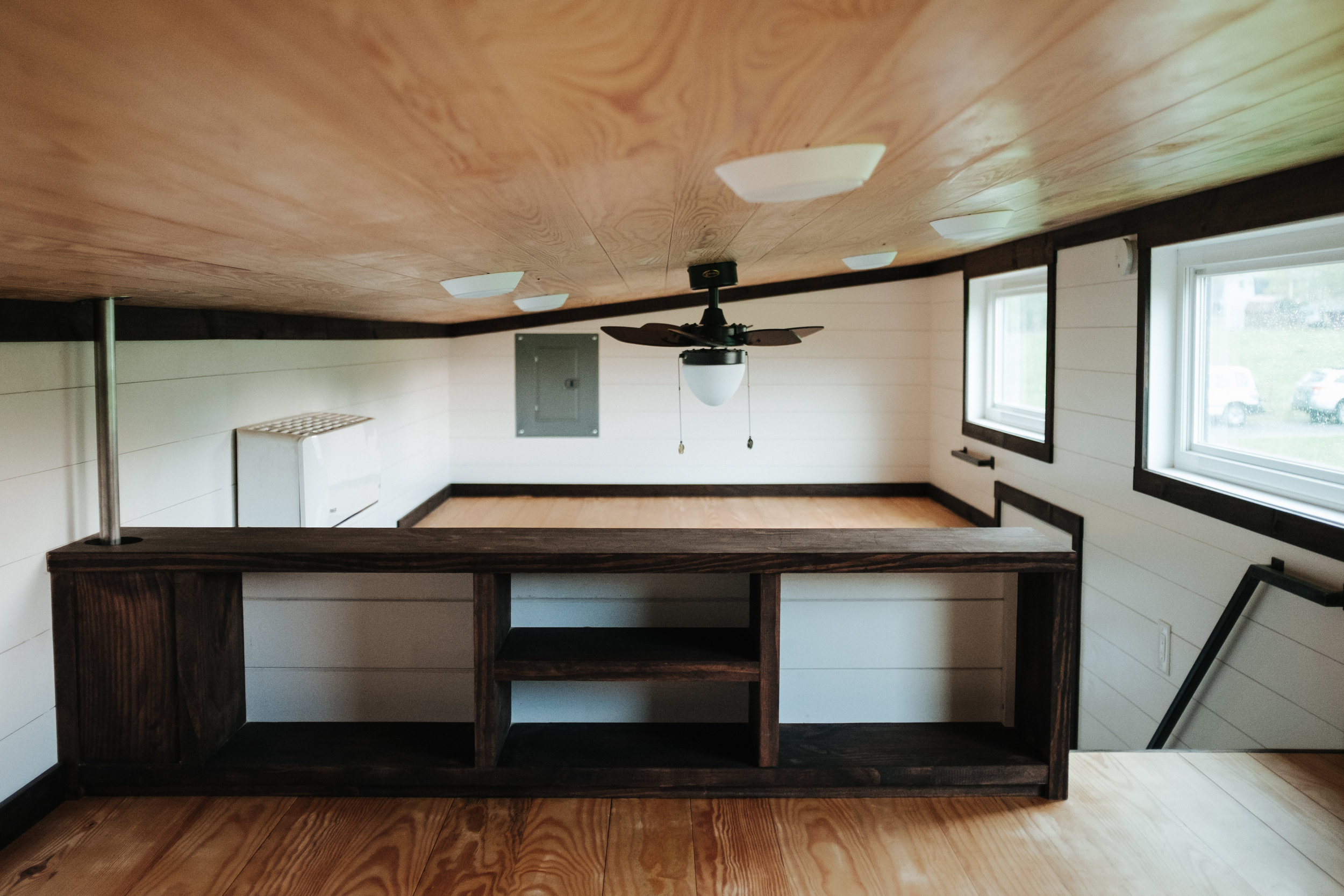 The Ironclad by Wind River Tiny Homes - loft open shelves, natural pine ceiling, LED lights, ship lap