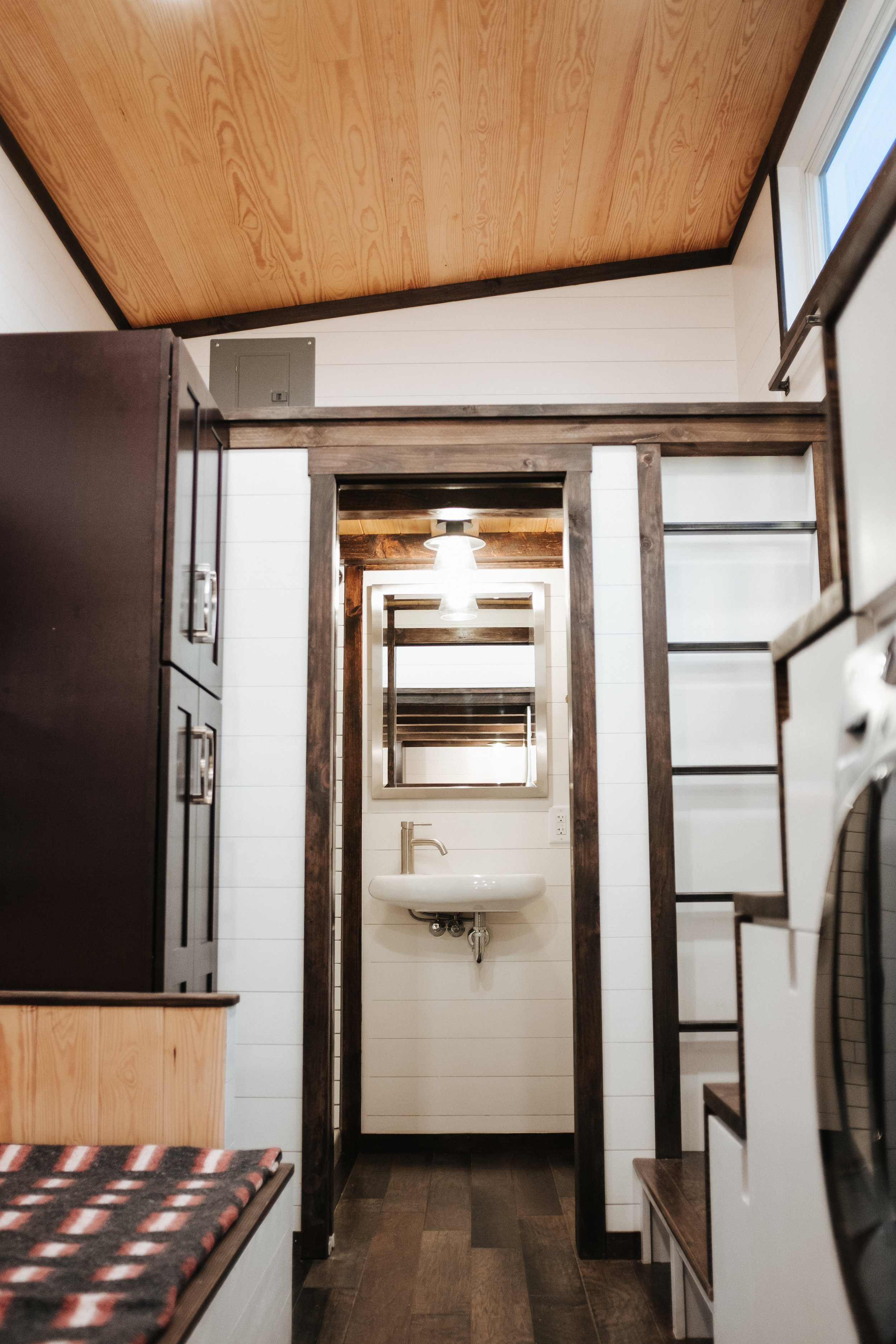 The Ironclad by Wind River Tiny Homes - custom storage stairs, storage couch, shaker style closet, built in steel ladder, floating sink