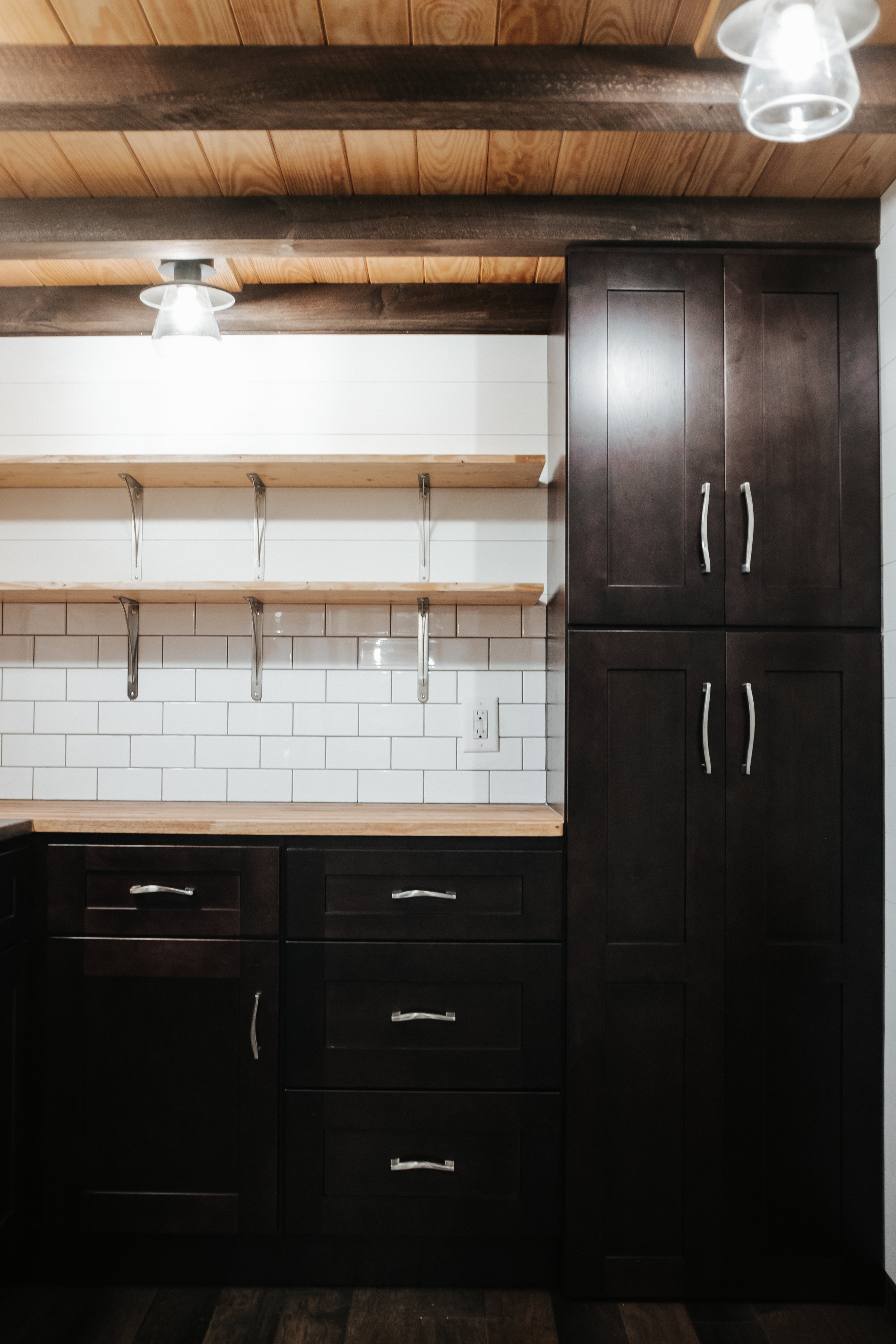 The Ironclad by Wind River Tiny Homes - shaker cabinets, butcher block counter, stainless hardware, subway tile, open shelving, natural pine ceiling