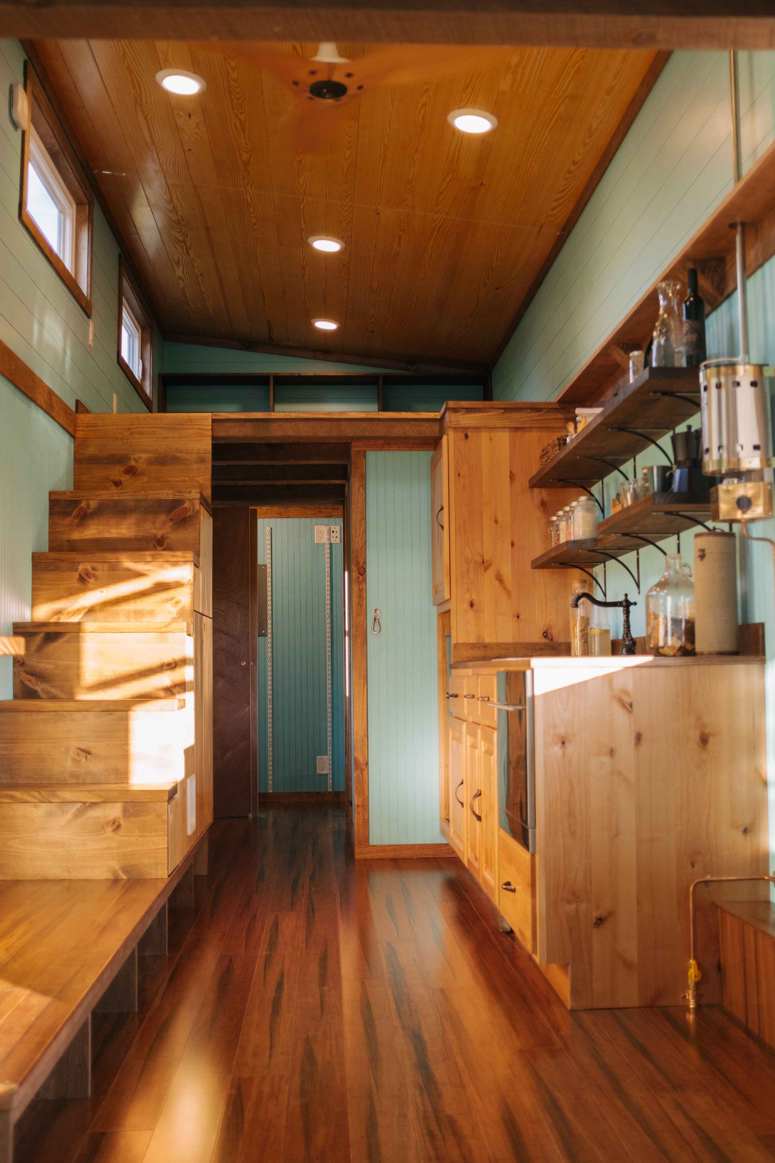 The Big Whimsy by Wind River Tiny Homes - built in storage stairs, Haiku ceiling fan, custom penny counter top, bamboo flooring, custom lily pad spiral stairs, cozy cabin propane heater
