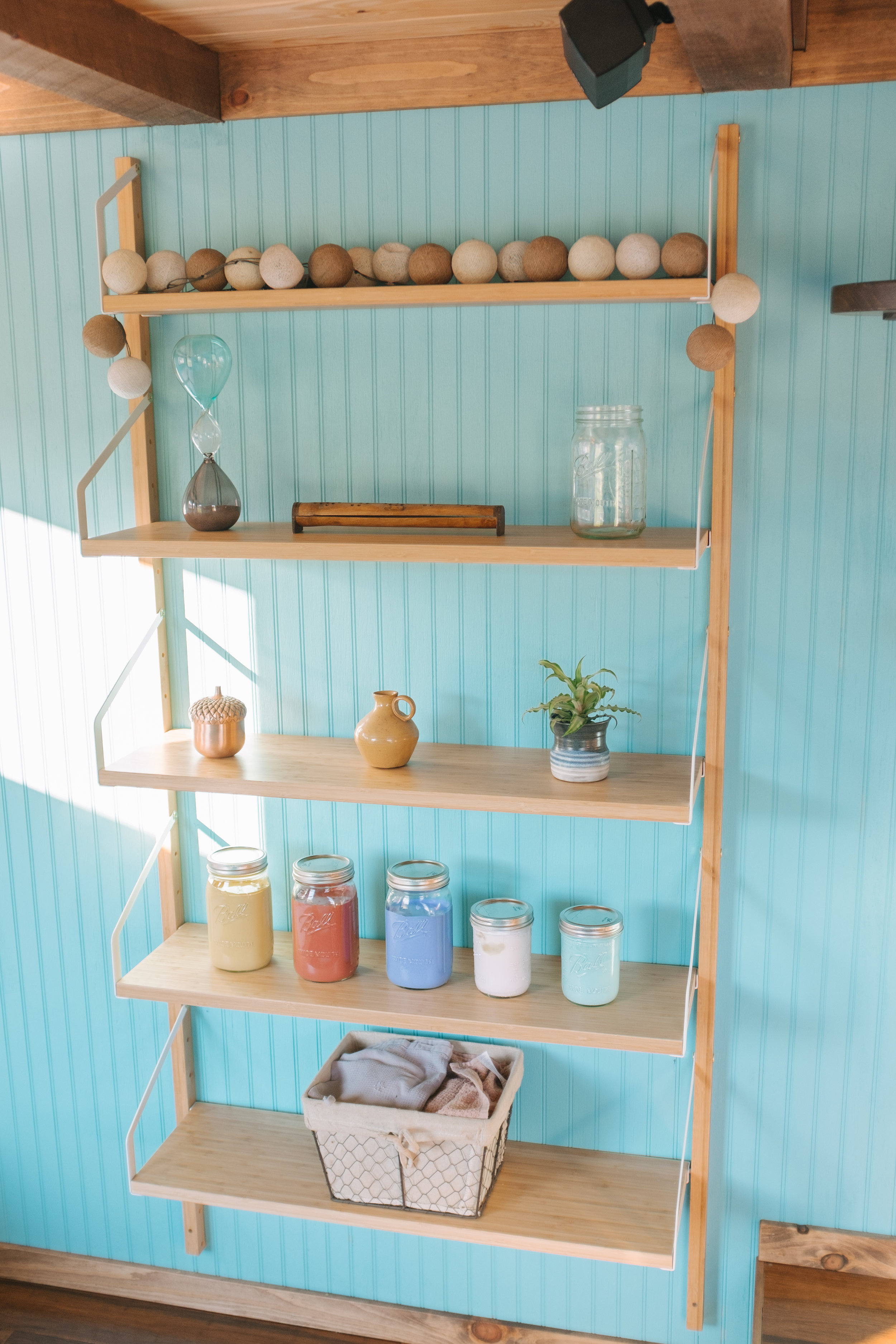 The Big Whimsy by Wind River Tiny Homes - bead board siding, IKEA shelving, custom lily pad spiral stairs