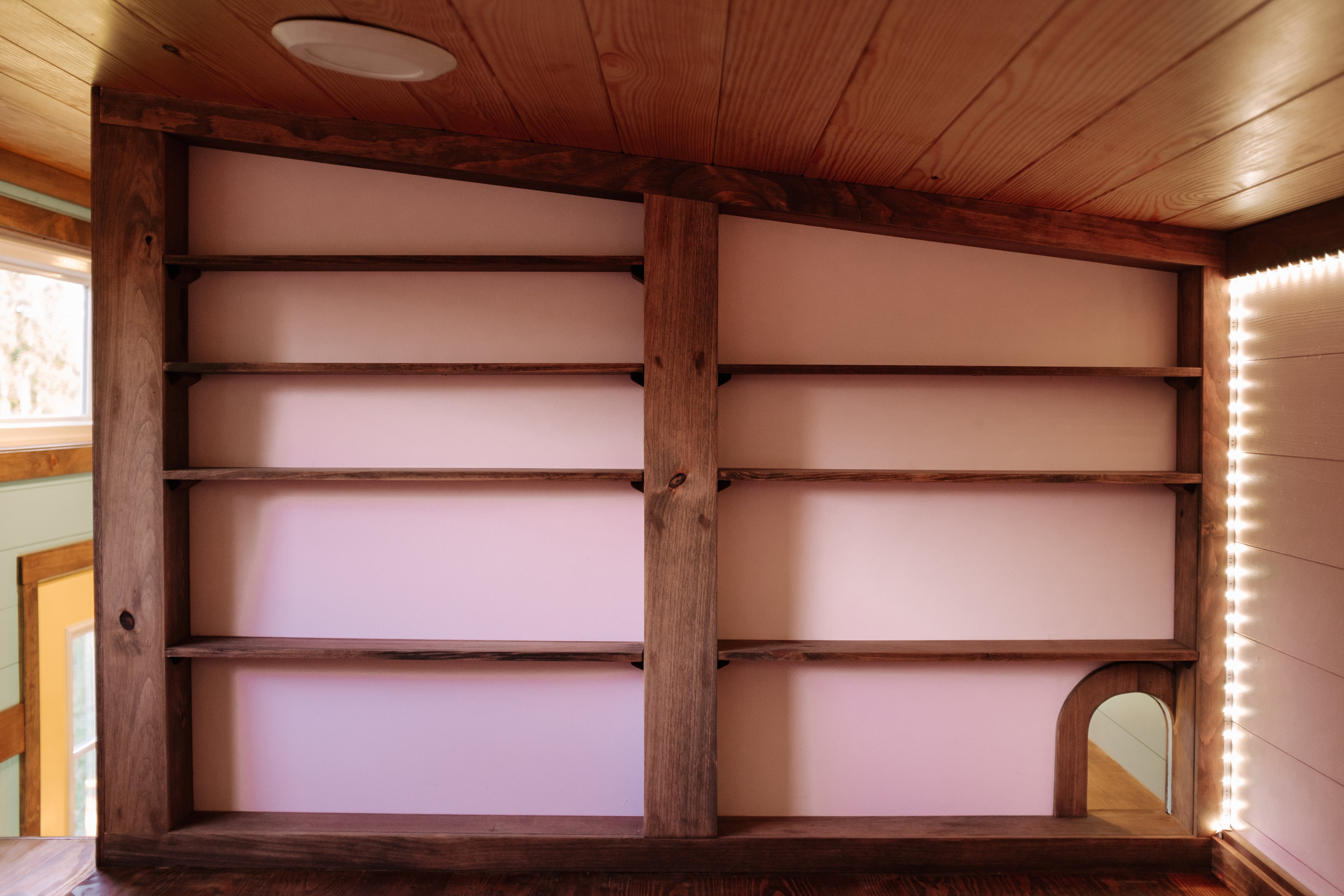 The Big Whimsy by Wind River Tiny Homes - secondary loft bedroom, natural yellow pine ceiling, LED accent lighting, cat door, catwalk to primary loft