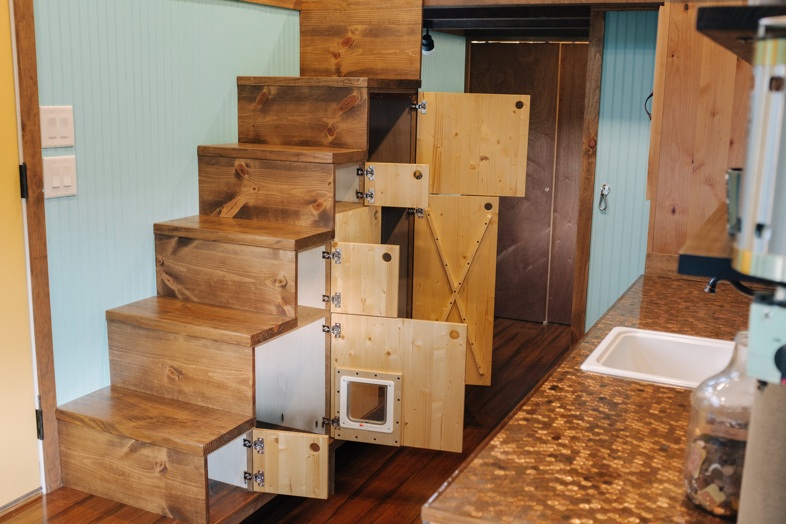 The Big Whimsy by Wind River Tiny Homes - built in storage shelving, cat door, litter box cubby with vent fan, custom penny counter top, bamboo flooring