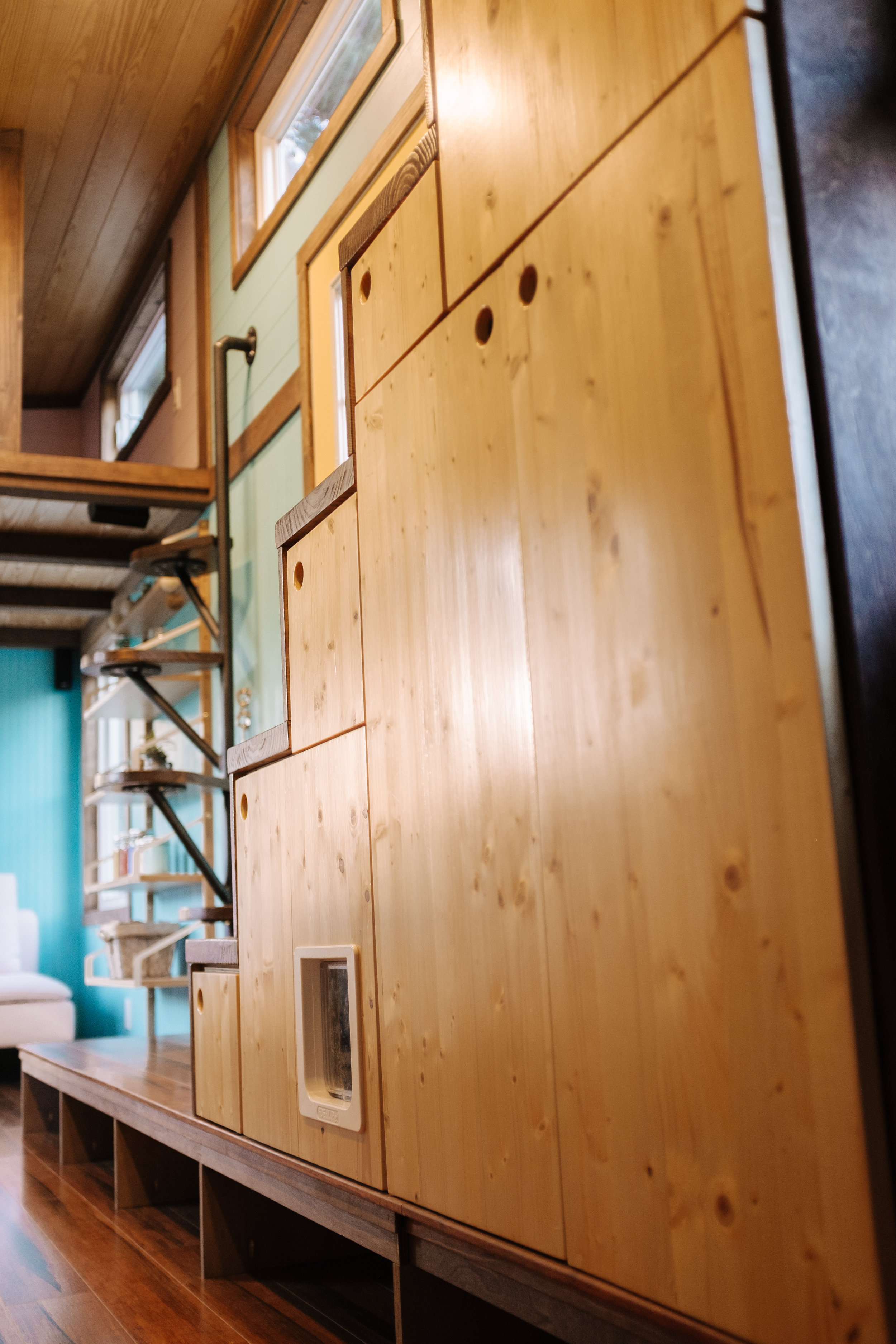 The Big Whimsy by Wind River Tiny Homes - built in storage stairs, custom lily pad spiral stairs, bamboo flooring, cat door, litter box cubby with vent fan