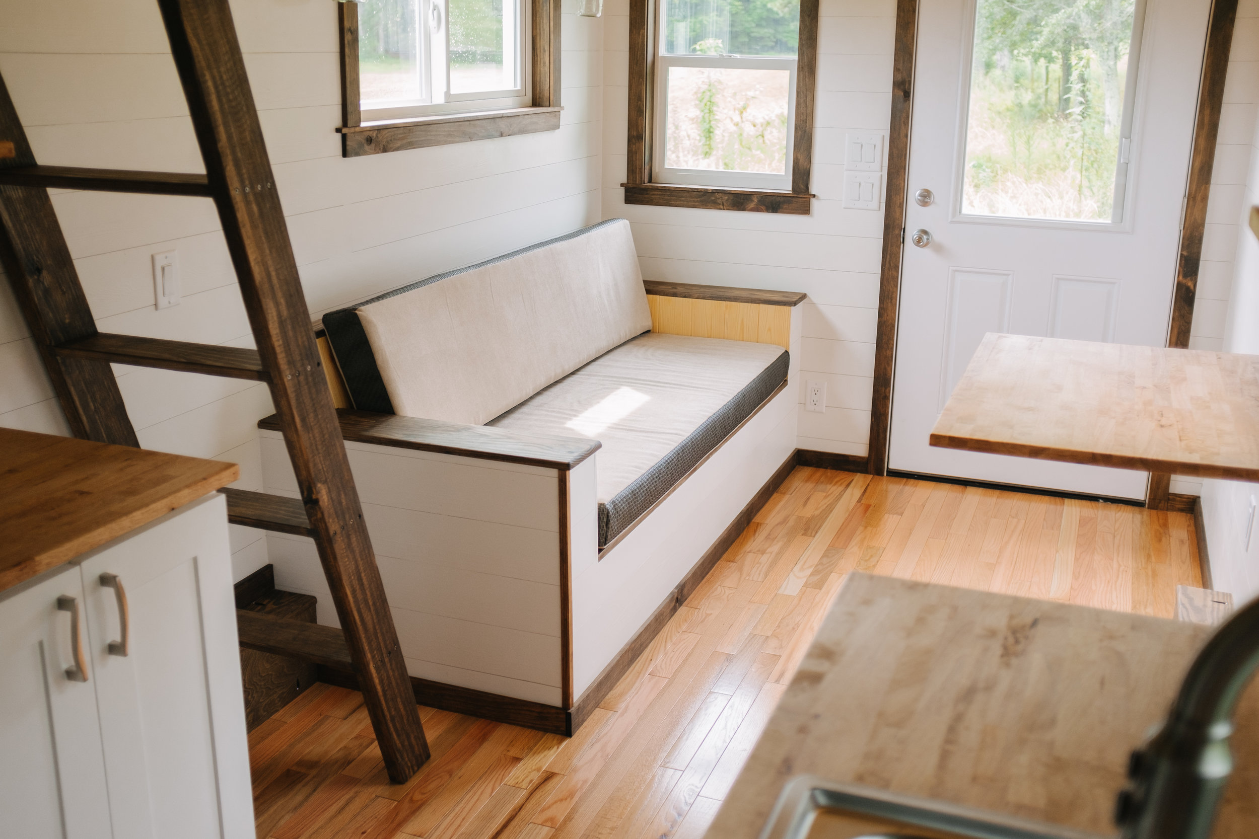 The Acadia by Wind River Tiny Homes - tiny house, ship lap, storage couch, oak hardwood floor, shaker cabinets, fold down table