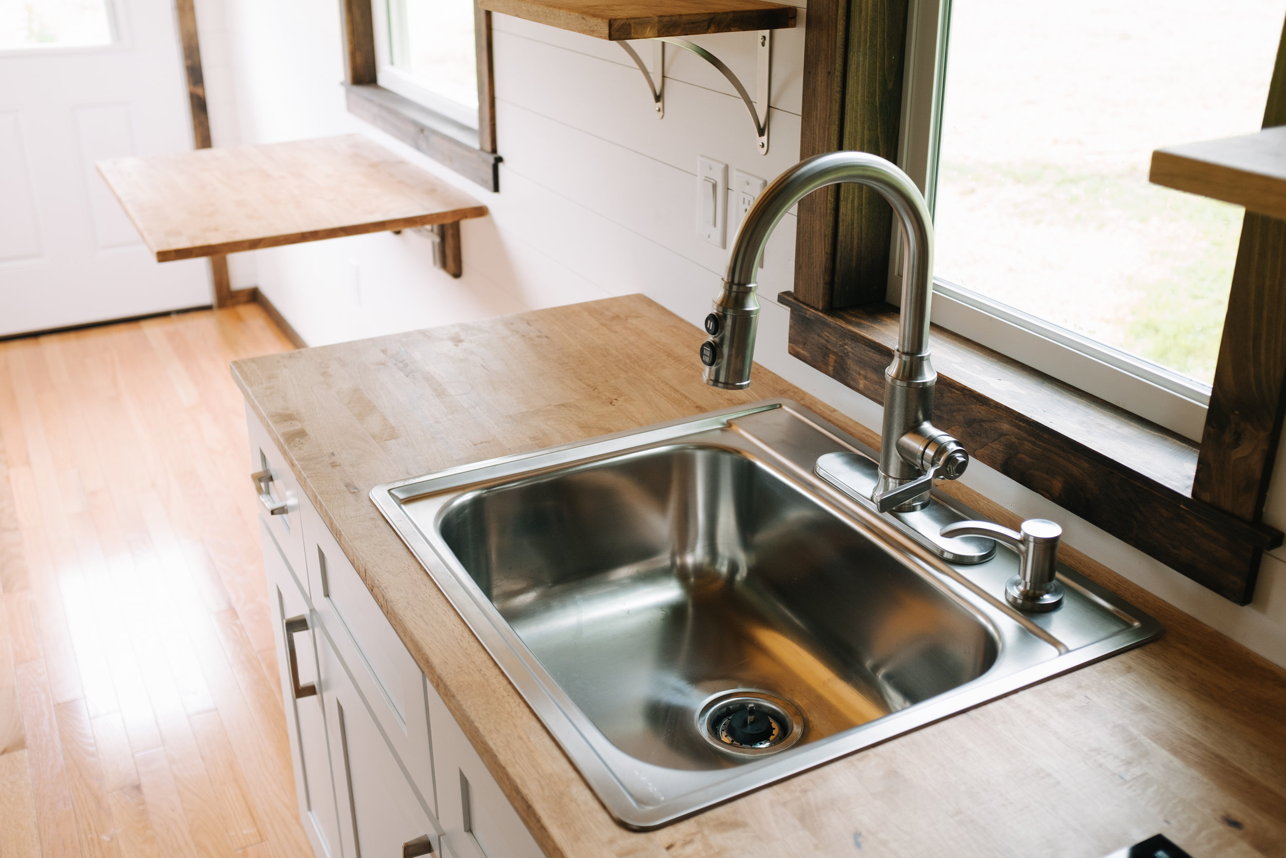 The Acadia by Wind River Tiny Homes - tiny house, butcher block counter top, Summit stove top, custom spice rack, stainless kitchen sink