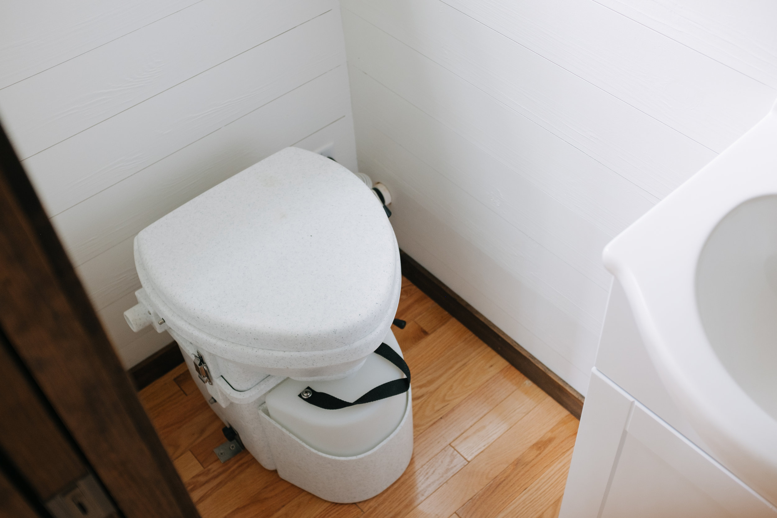 The Acadia by Wind River Tiny Homes - tiny house, pocket door, Natures Head composting toilet, bathroom vanity