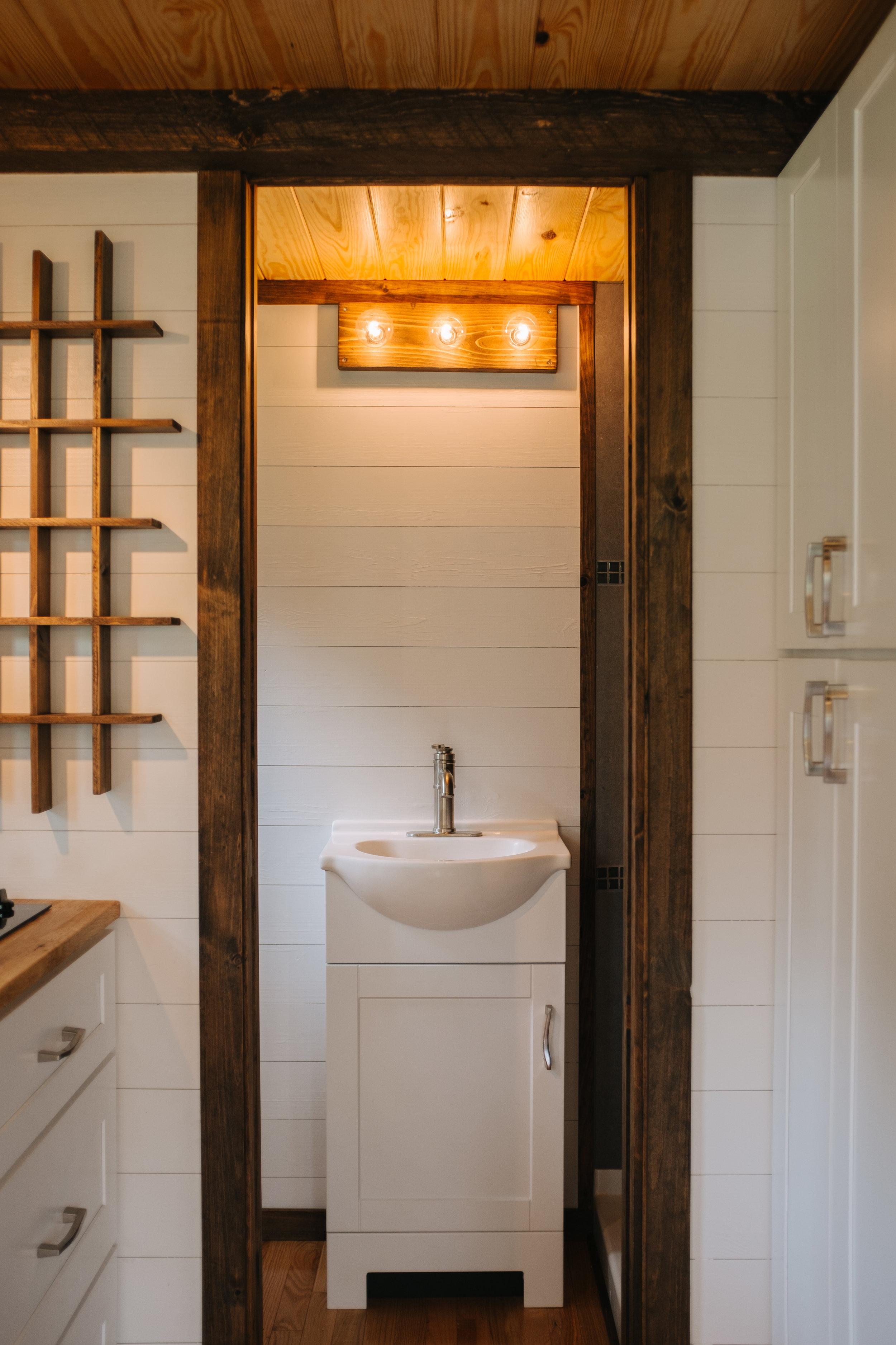 The Acadia by Wind River Tiny Homes - tiny house, shaker cabinets, custom spice rack, pocket door