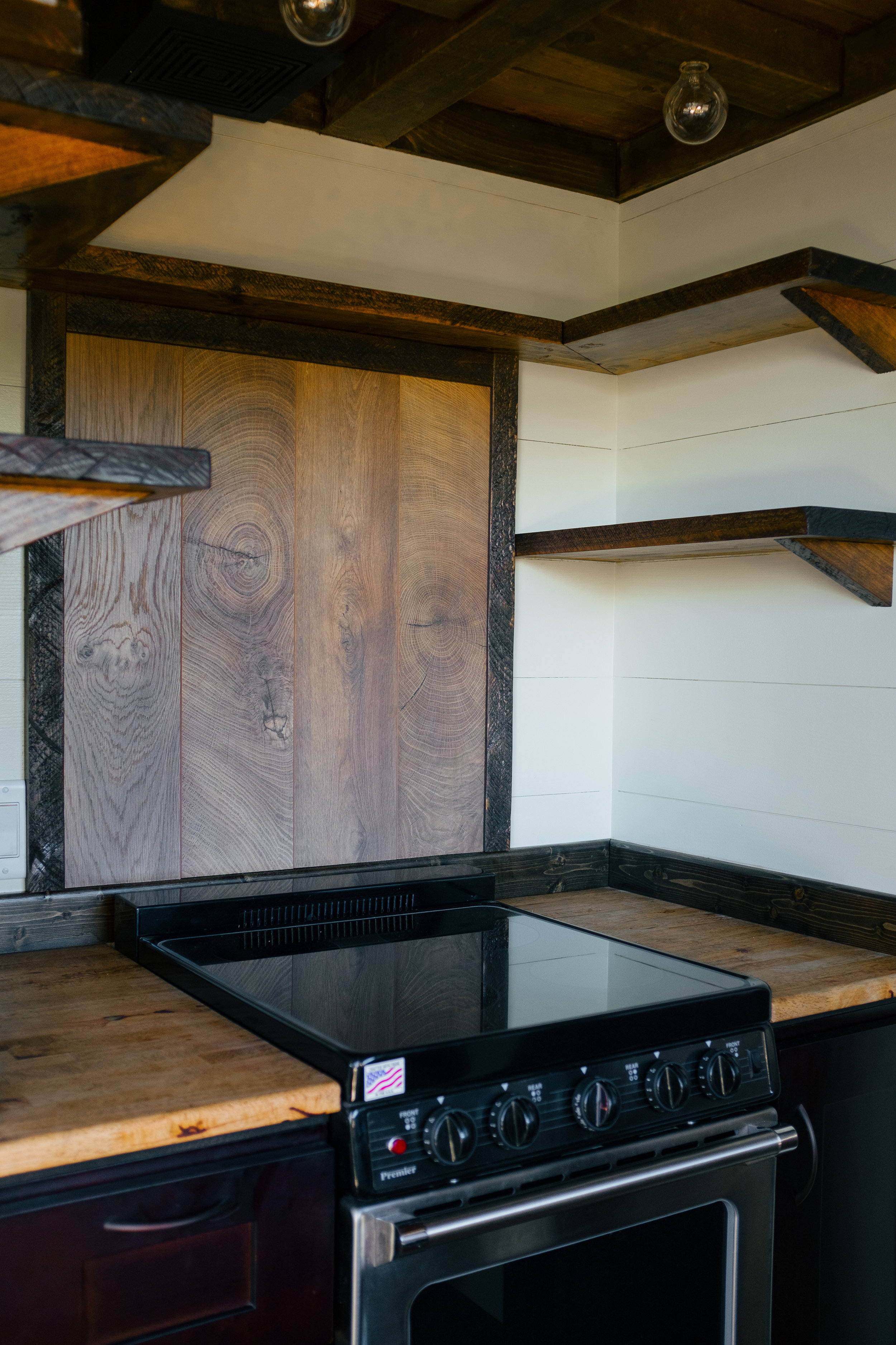 The Silhouette by Wind River Tiny Homes -shaker style cabinets, open kitchen shelving, butcher block, electric stove oven