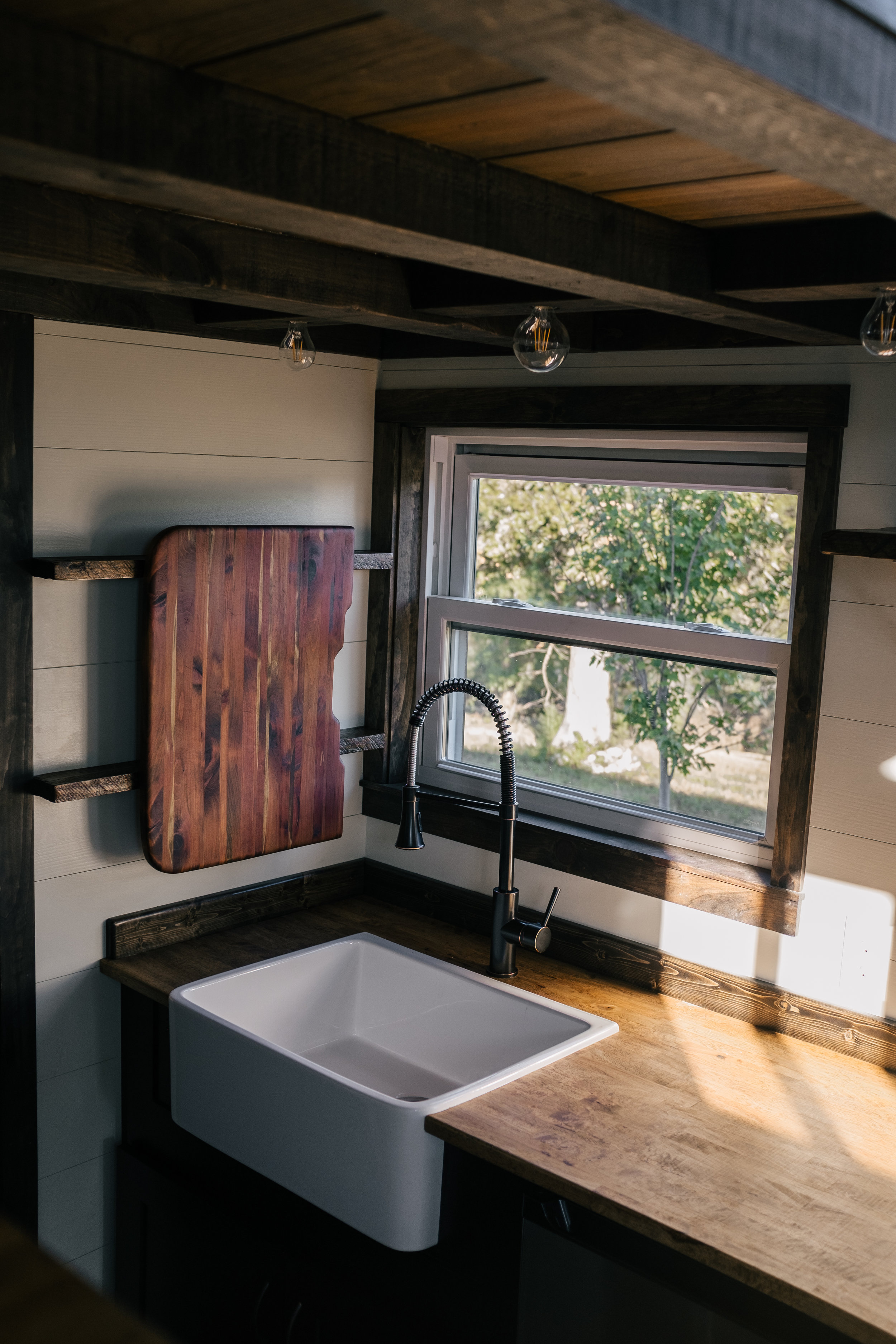 The Silhouette by Wind River Tiny Homes -shaker style cabinets, open kitchen shelving, under cabinet fridge, farmhouse sink, butcher block, cedar sink cutting board