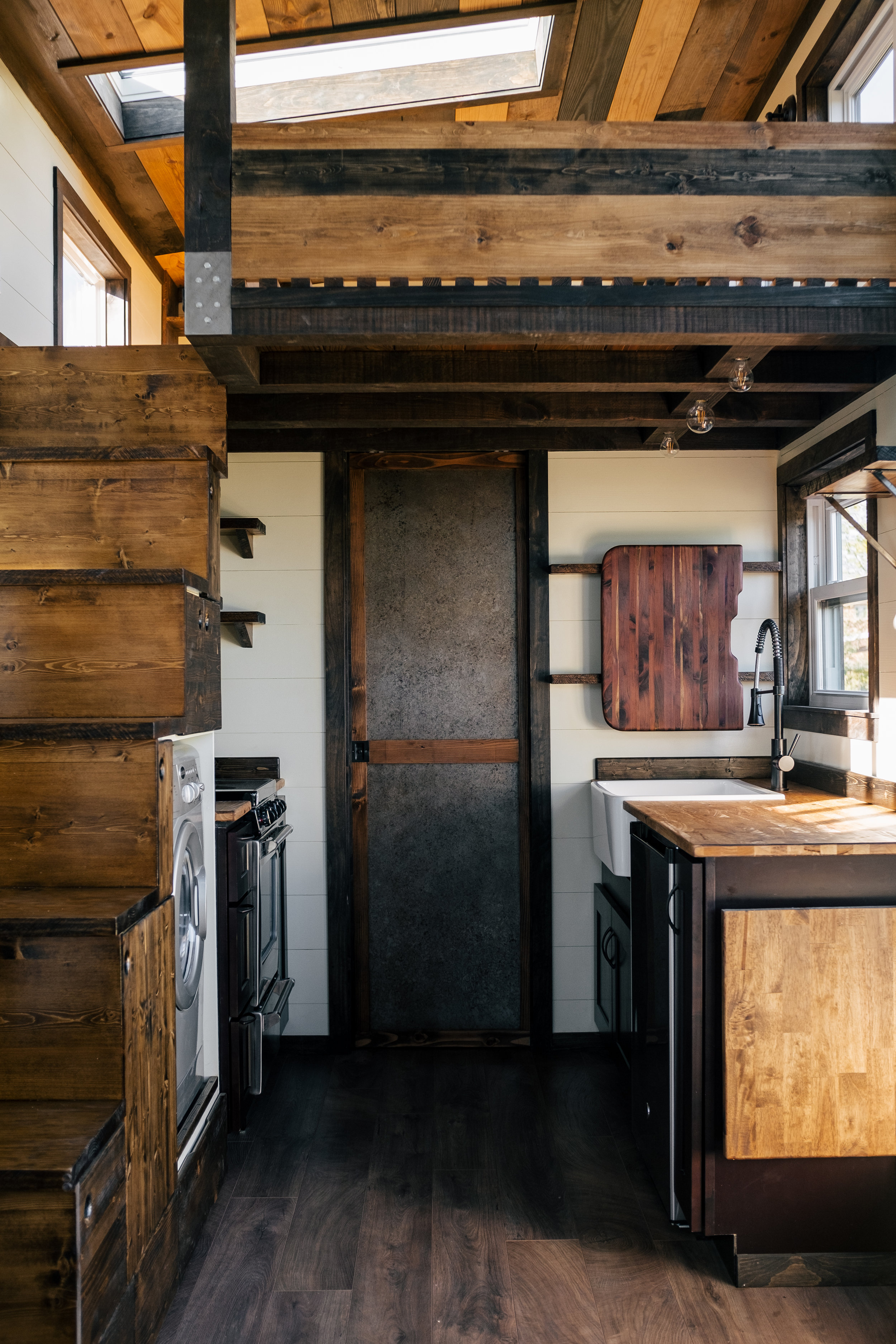 The Silhouette by Wind River Tiny Homes -shaker style cabinets, farmhouse sink, cedar sink cutting board, fold down table, storage stairs, patina steel pocket door