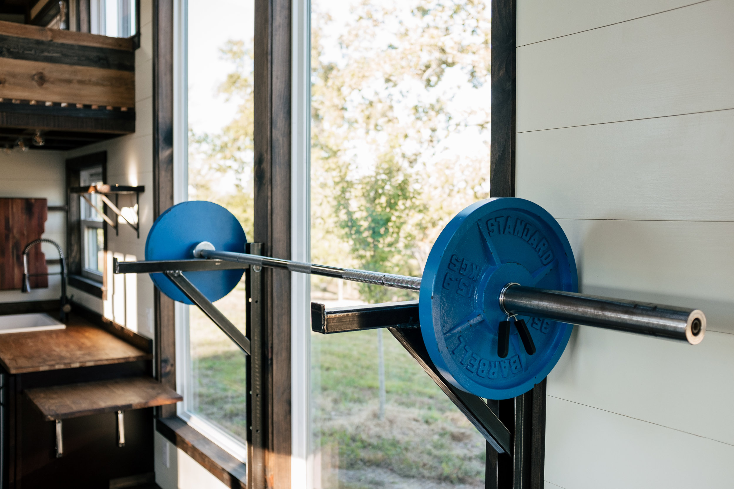 The Silhouette by Wind River Tiny Homes - custom olympic squat/bench rack, gym rings, integrated exercise floor