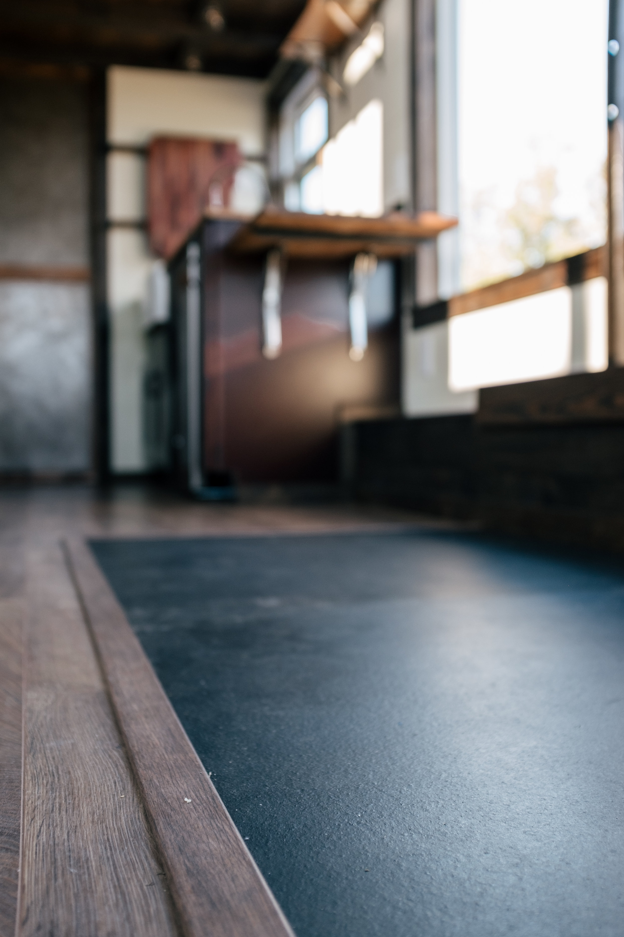 The Silhouette by Wind River Tiny Homes - integrated exercise floor, custom Olympic squat/bench rack, fold down table