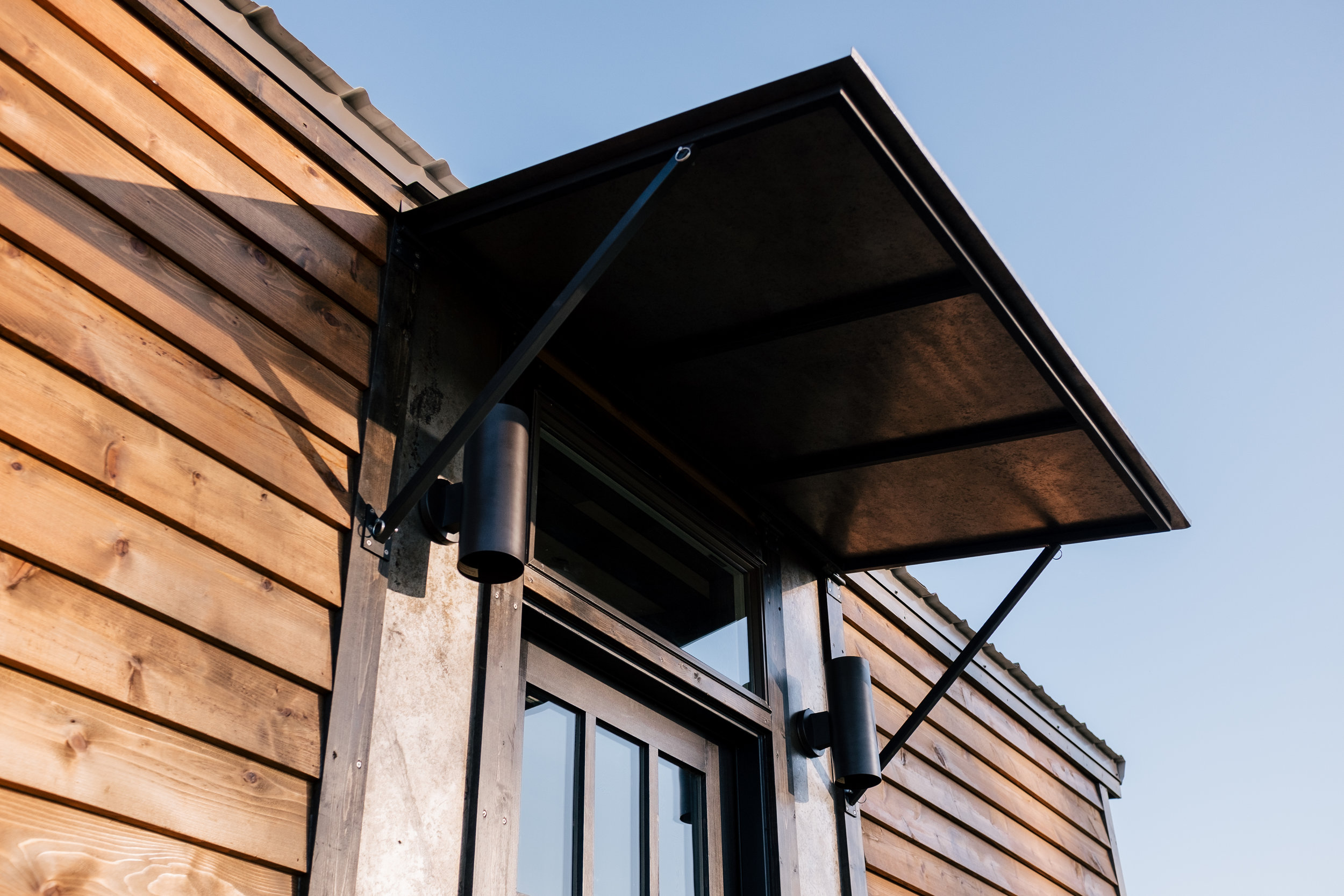 The Silhouette by Wind River Tiny Homes - rustic, cedar siding, patina steel clad siding, fold down awning