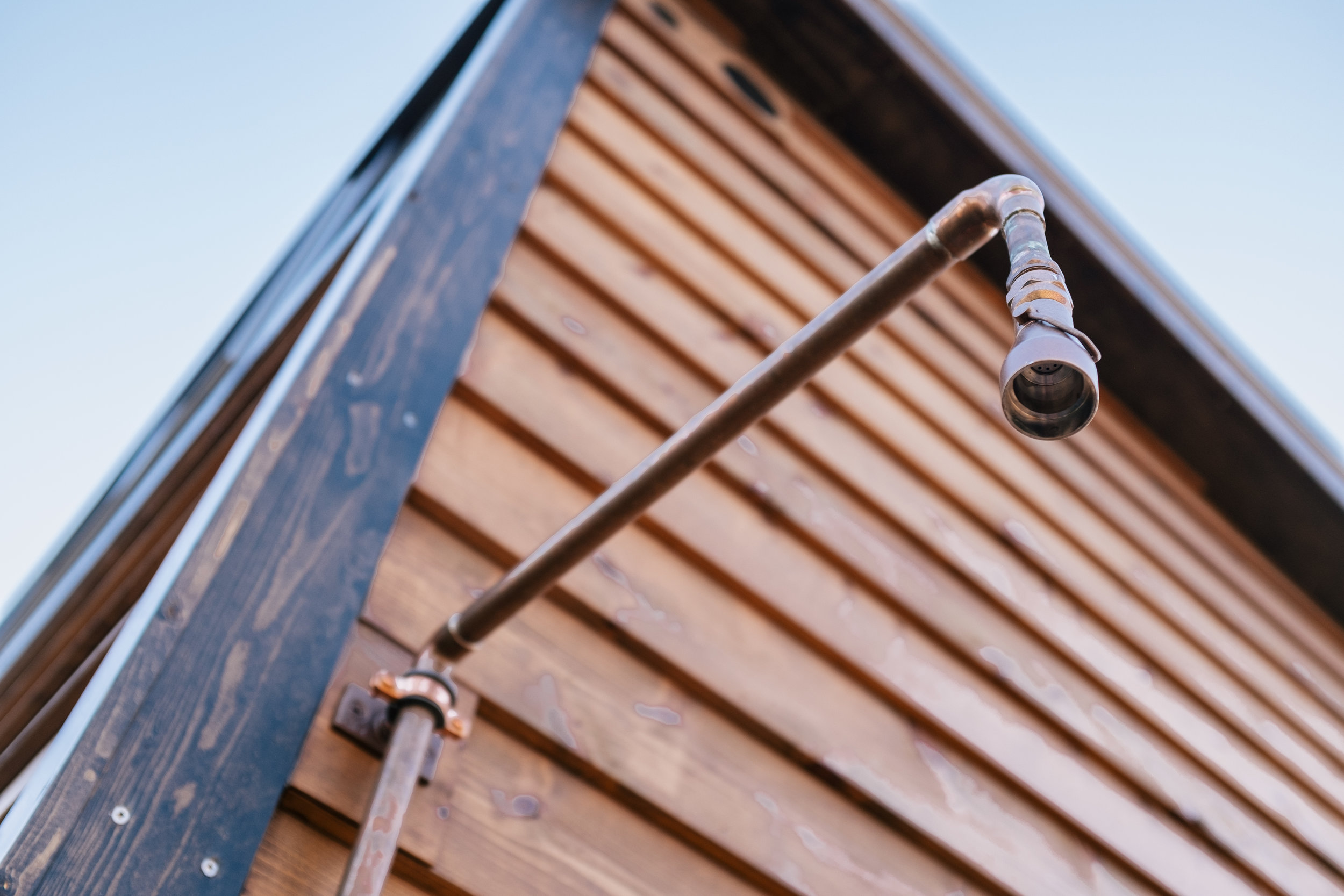 The Silhouette by Wind River Tiny Homes - rustic, cedar siding, patina steel clad siding, exterior copper swivel shower