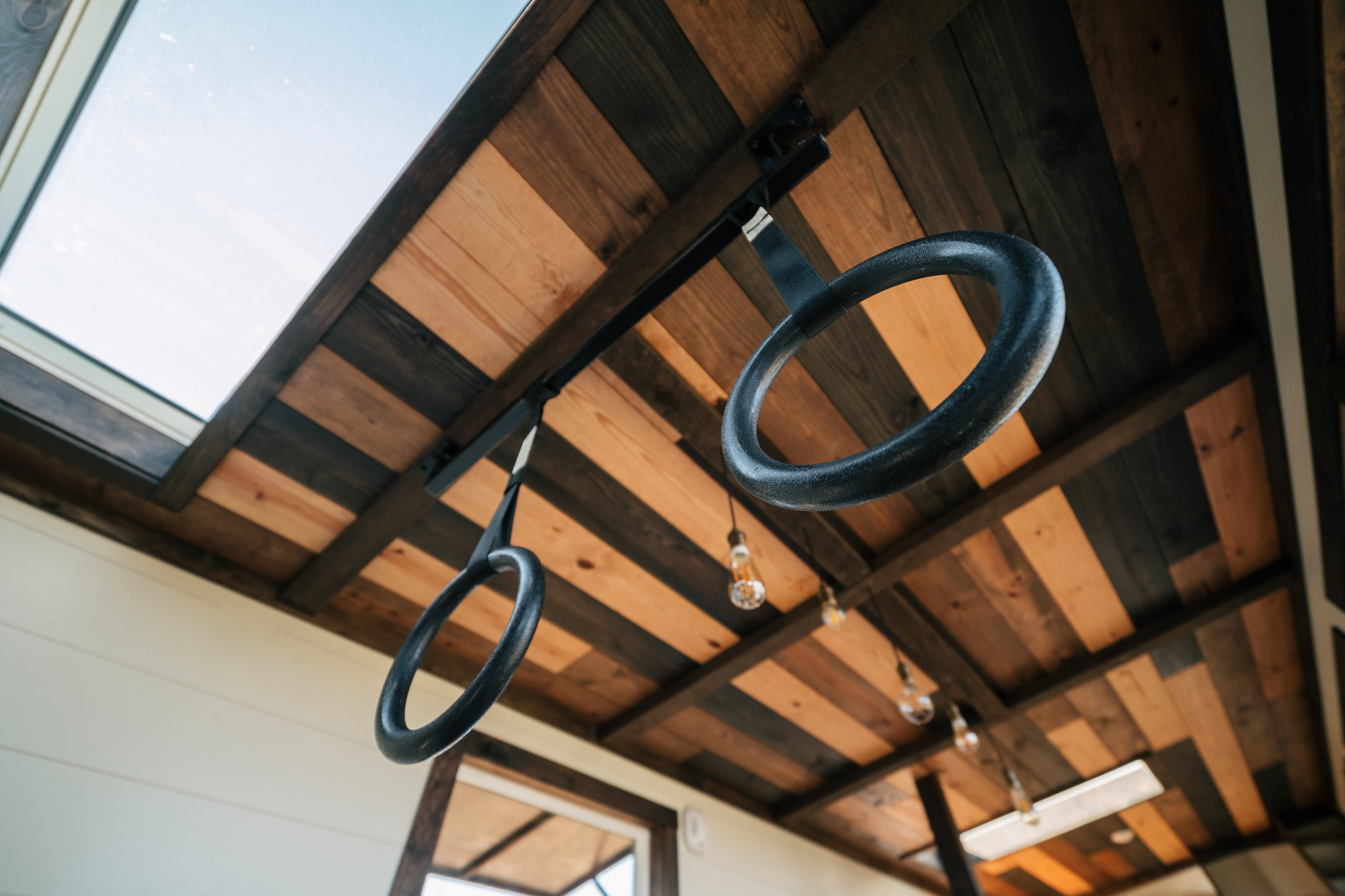The Silhouette by Wind River Tiny Homes - multi stained tongue & groove ceiling, gym rings, skylight