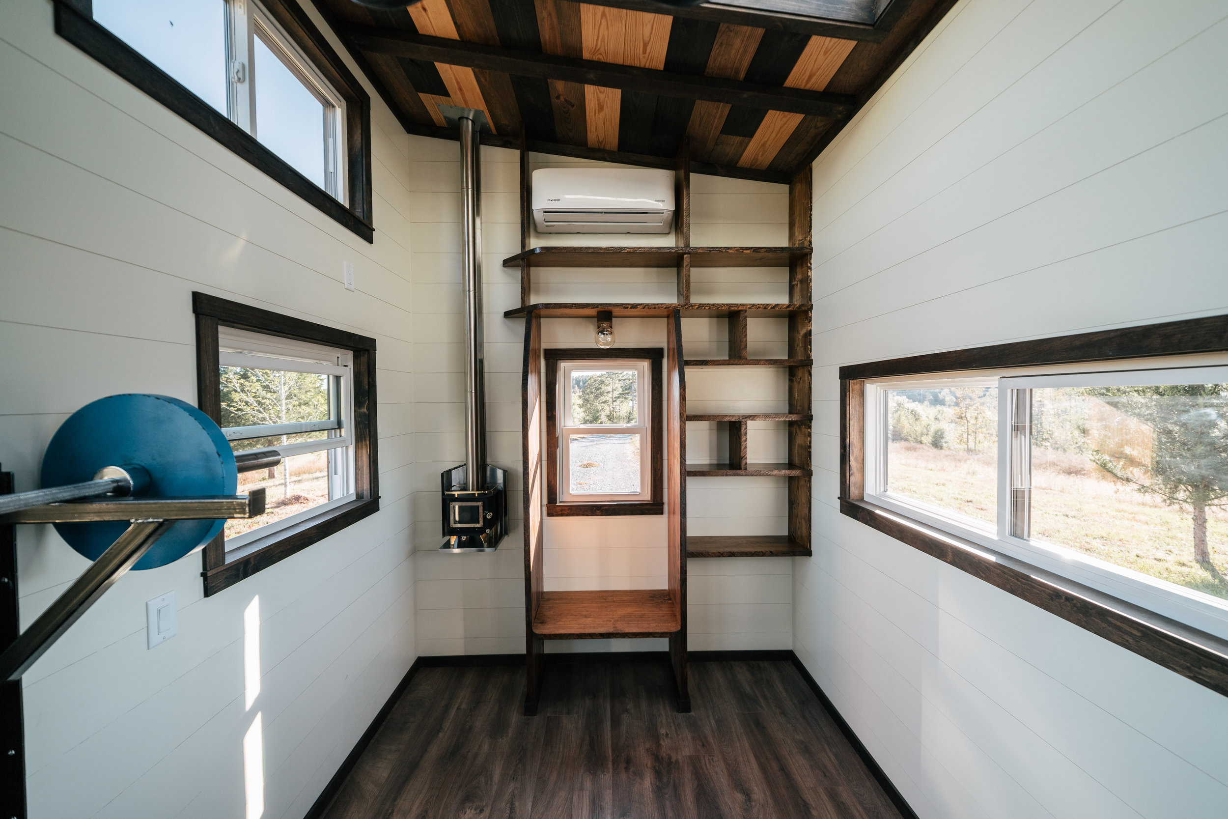 The Silhouette by Wind River Tiny Homes - custom olympic squat/bench rack, gym rings, integrated exercise floor, Cubic Mini wood stove