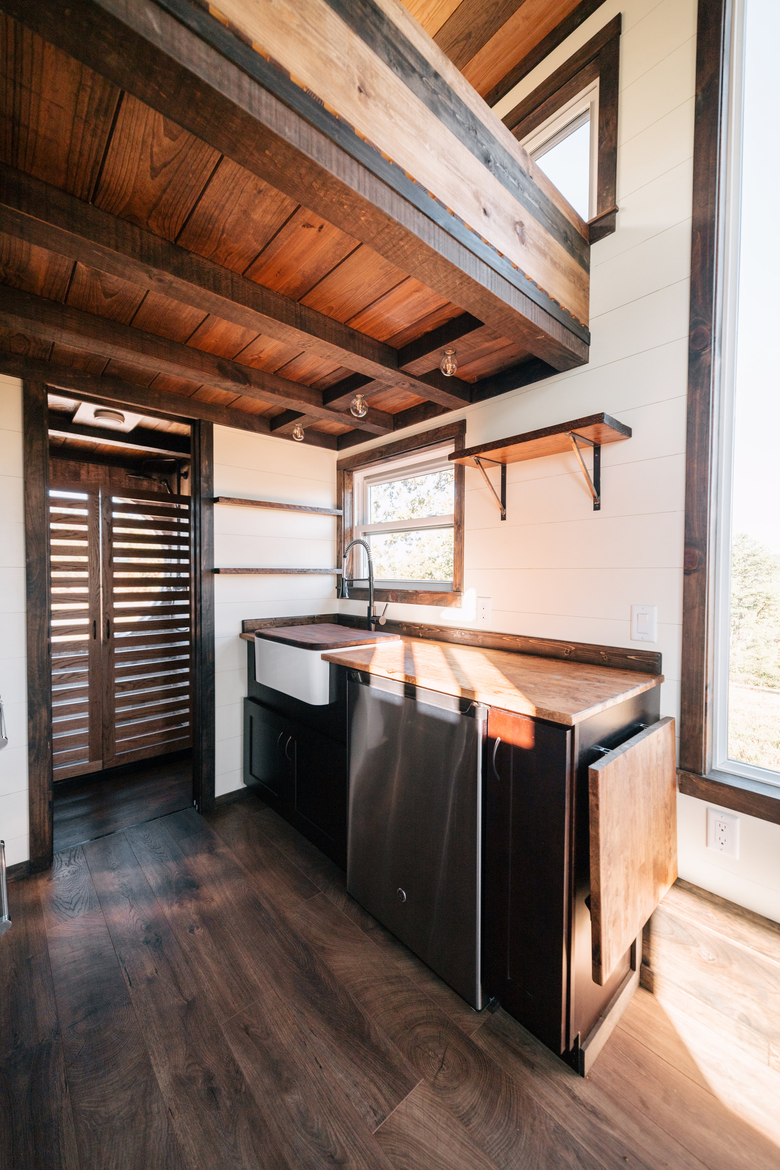 The Silhouette by Wind River Tiny Homes - fold down table, shaker style cabinets, open kitchen shelving, under cabinet fridge, farmhouse sink, butcher block