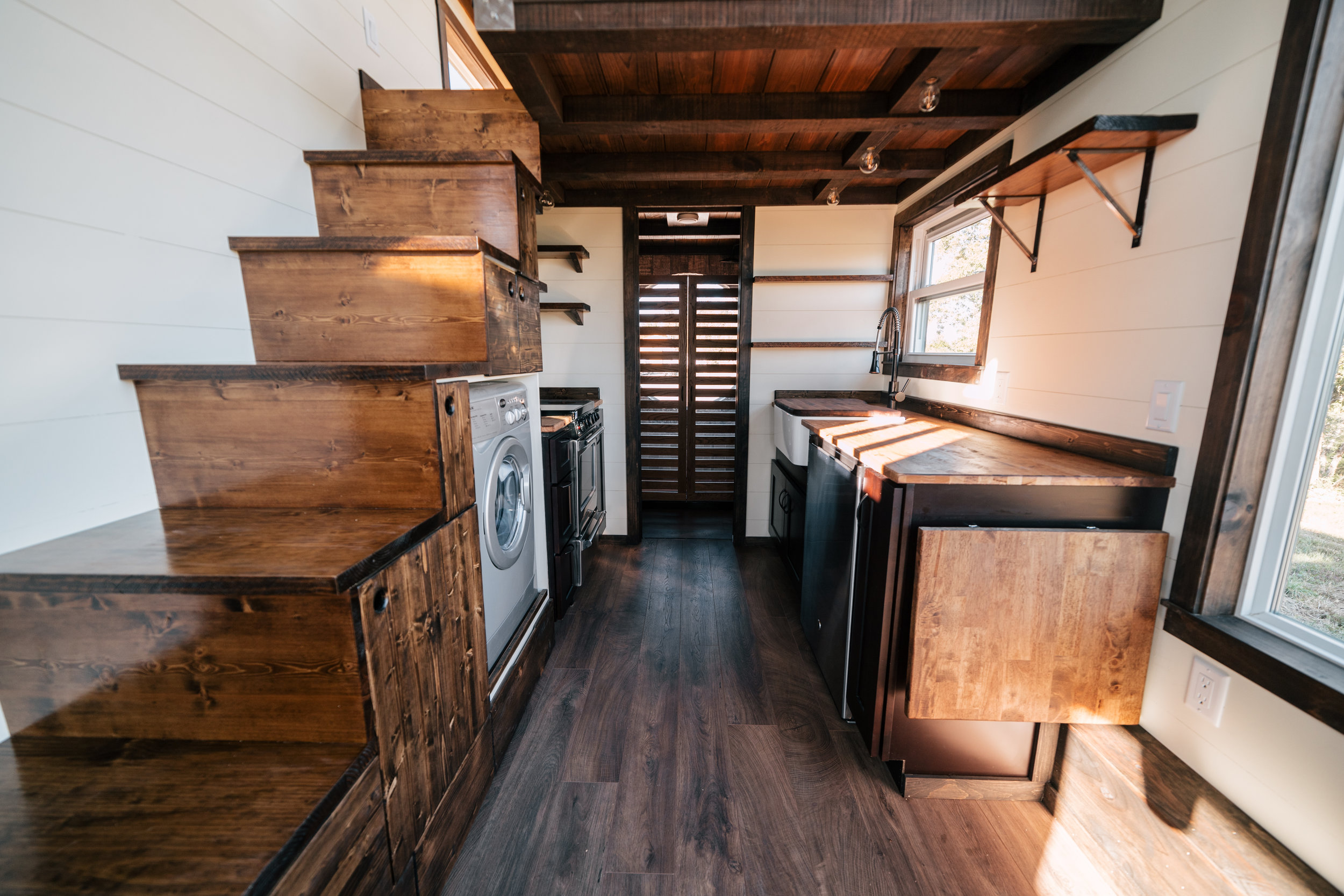 The Silhouette by Wind River Tiny Homes - ship lap, fold down table, storage stairs, open kitchen shelving