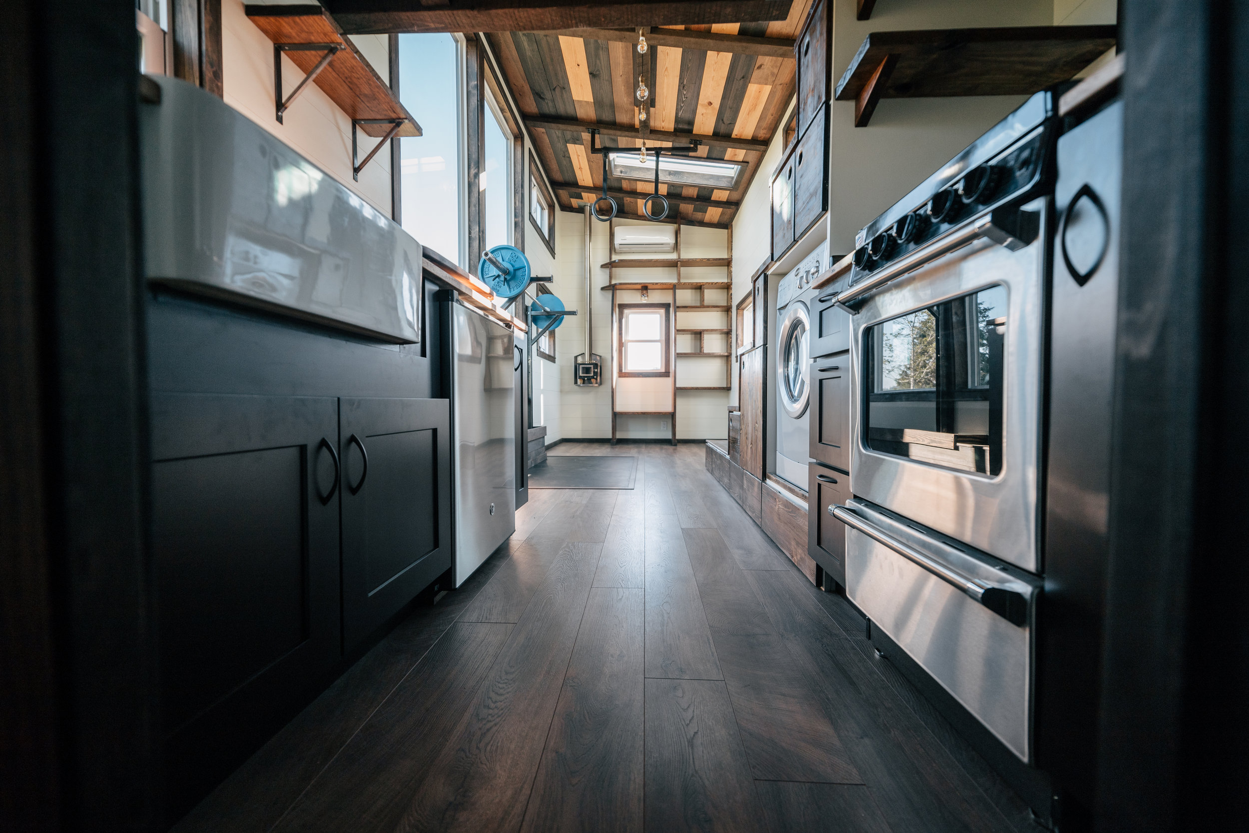 The Silhouette by Wind River Tiny Homes -custom Olympic squat/bench rack, washer dryer combo,storage stairs, gym rings, shaker style cabinets,multi stained ceiling