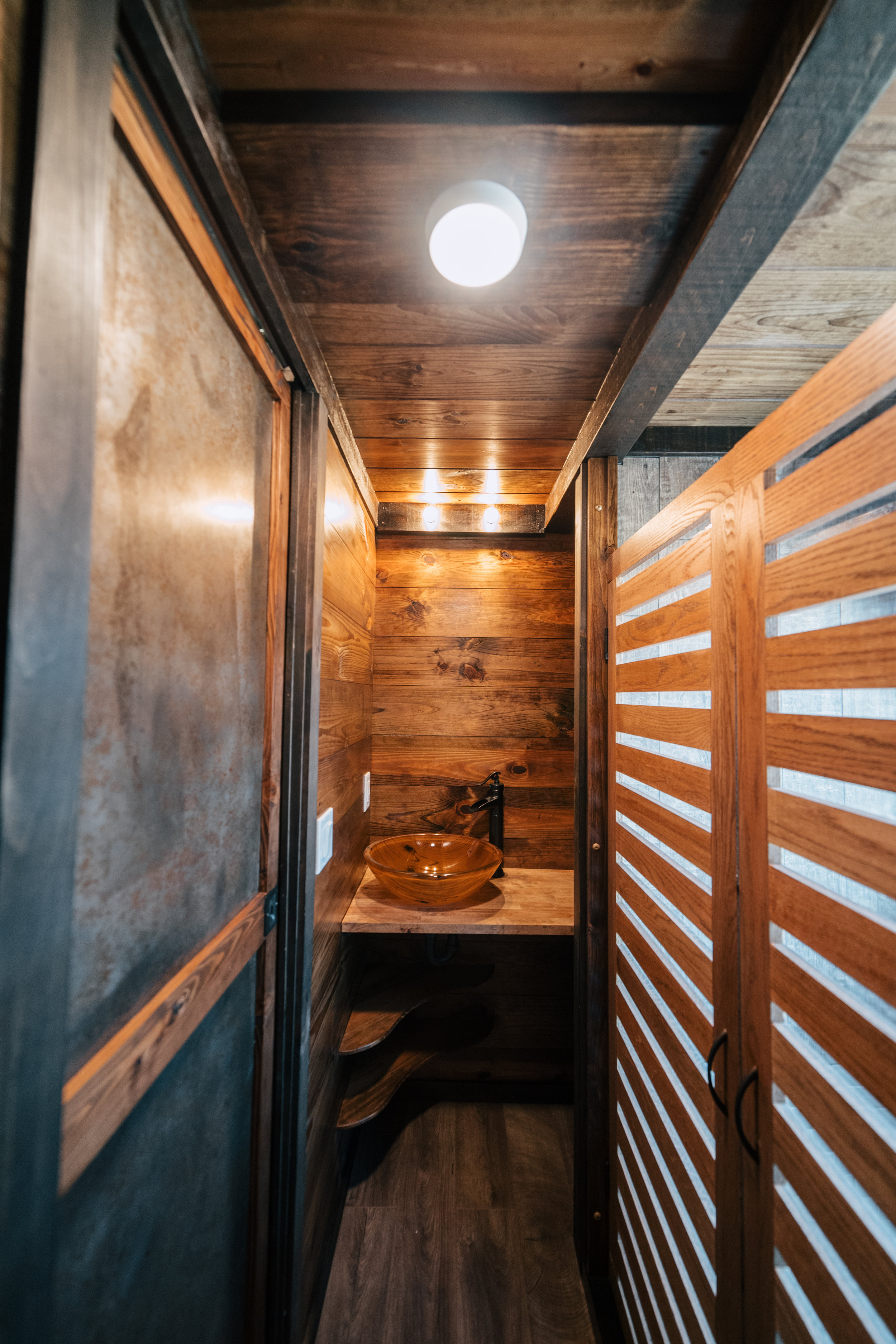 The Silhouette by Wind River Tiny Homes - patina steel pocket door, glass vessel sink, oak wood slat/Plexiglass shower stall doors