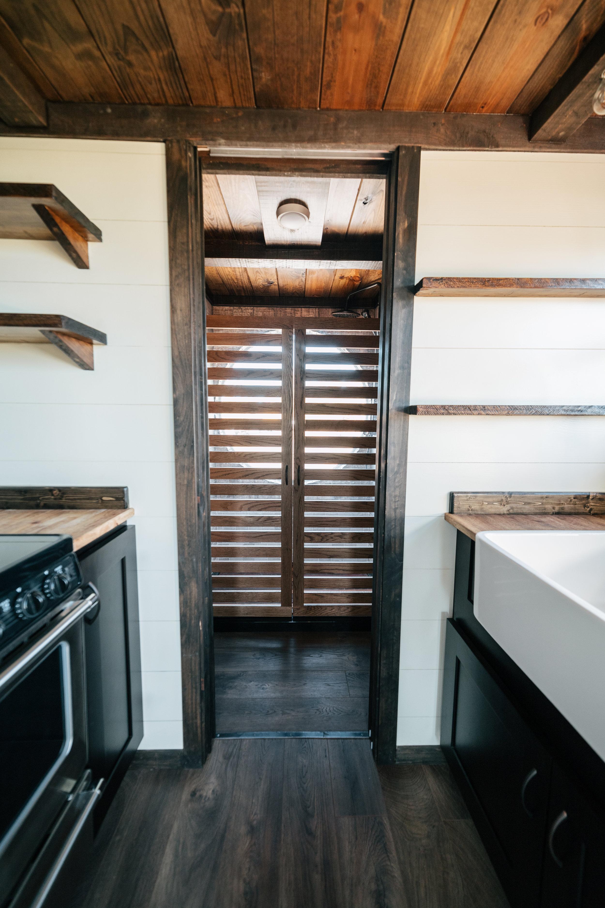 The Silhouette by Wind River Tiny Homes - patina steel pocket door, shaker style cabinets, oak wood slat/Plexiglass shower stall doors