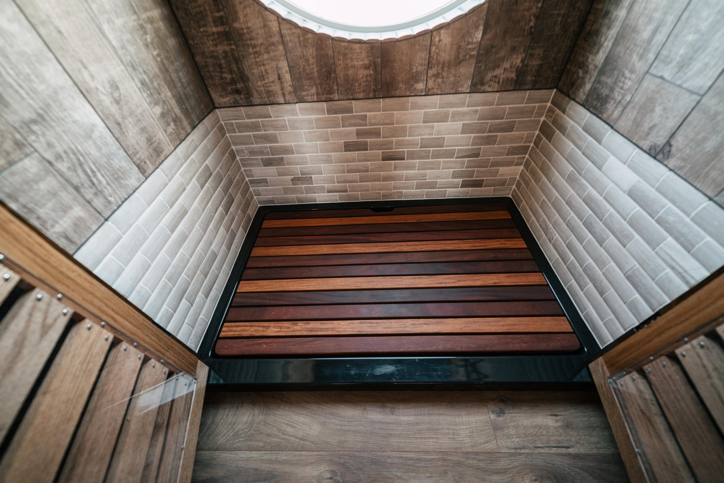 The Silhouette by Wind River Tiny Homes -oak wood slat/Plexiglass shower stall doors, limestone tile, faux wood tile, cumaru wood shower deck insert