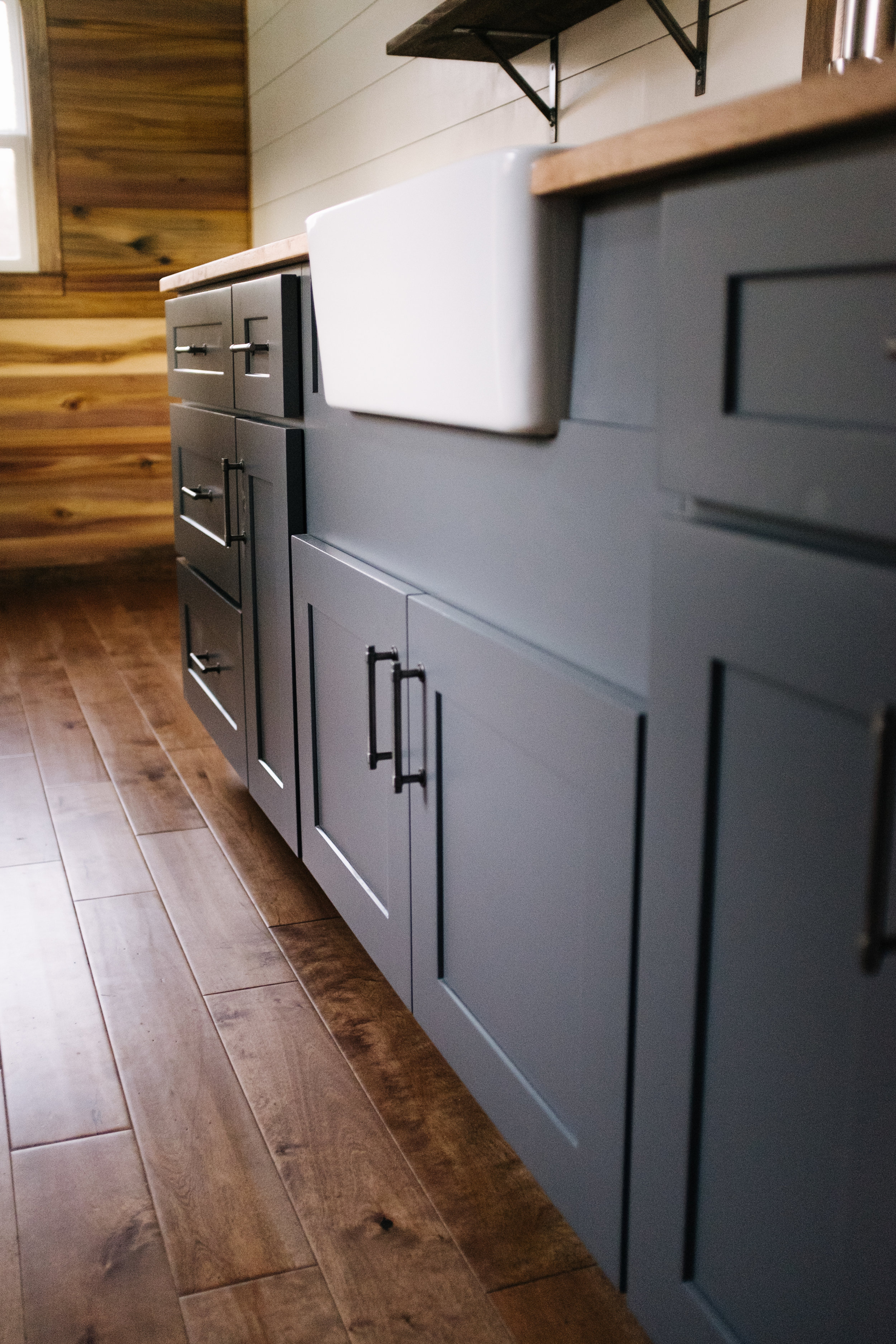 The Noah by Wind River Tiny Homes - natural poplar accent wall, shiplap, birch hardwood flooring, gray shaker cabinets, farmhouse sink, butcher block counter