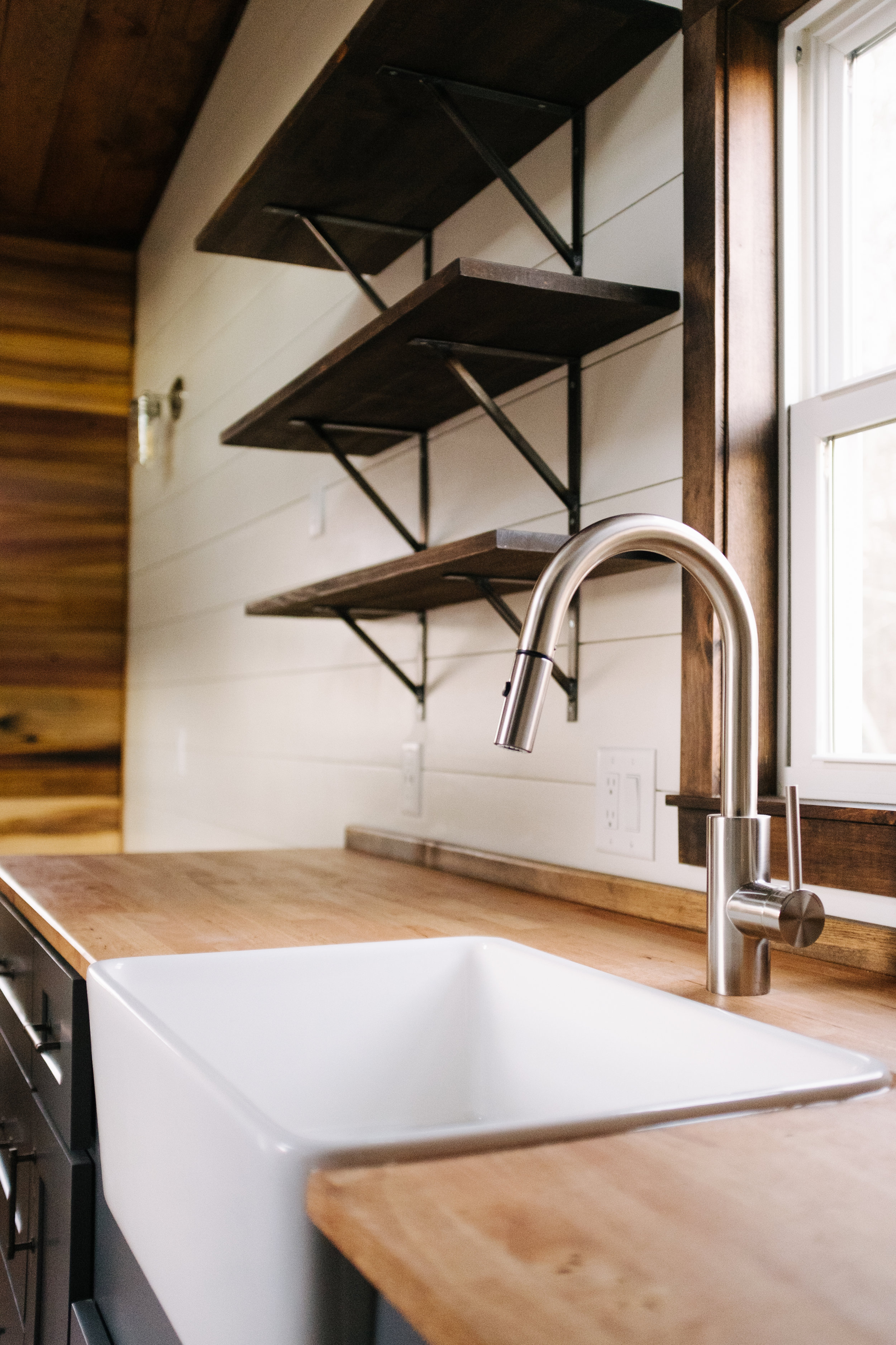 The Noah by Wind River Tiny Homes - natural poplar accent wall, shiplap, open shelving, gray shaker cabinets, farmhouse sink, butcher block counter