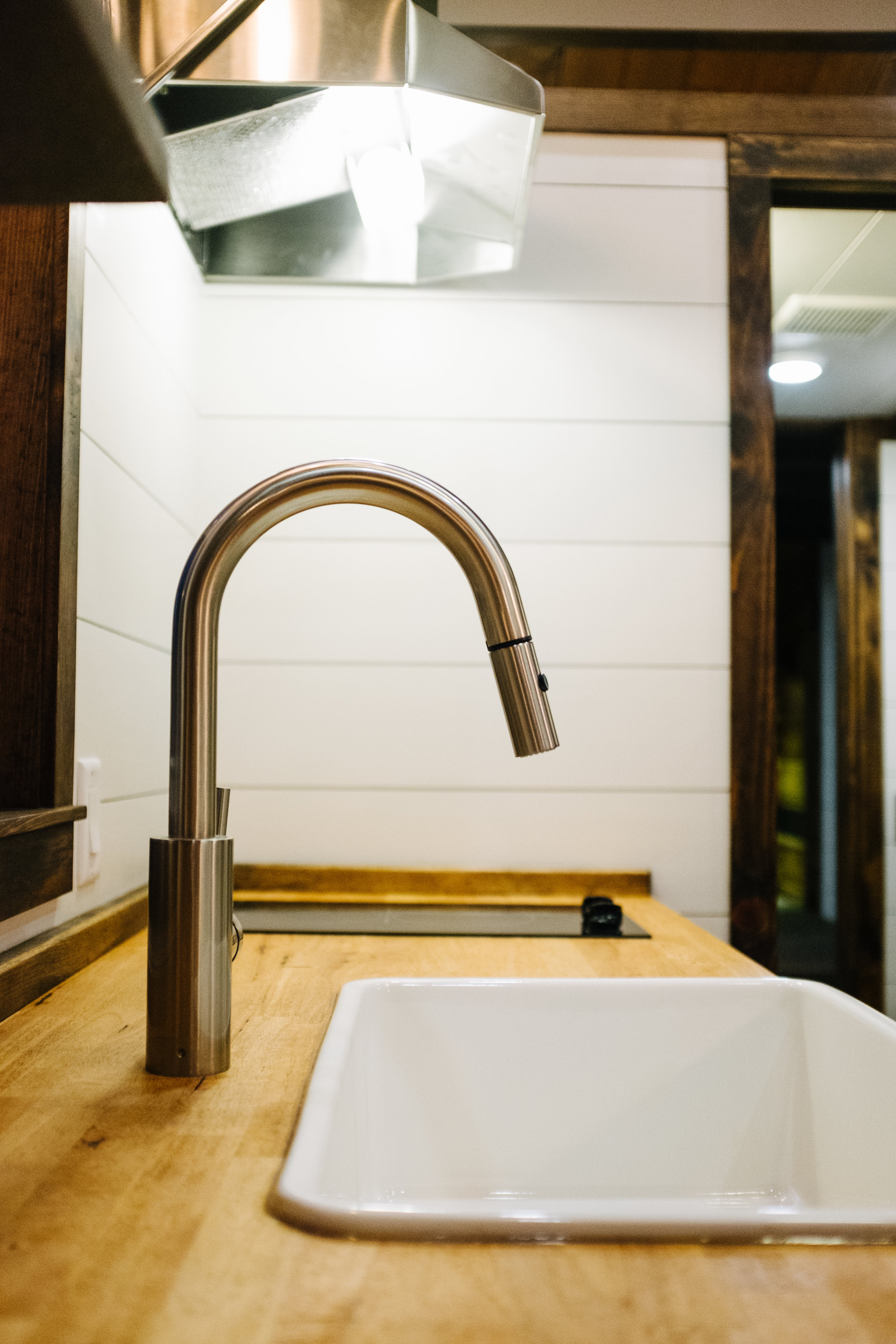 The Noah by Wind River Tiny Homes - farmhouse sink, butcher block counter, open shelving, shiplap, electric glass cooktop