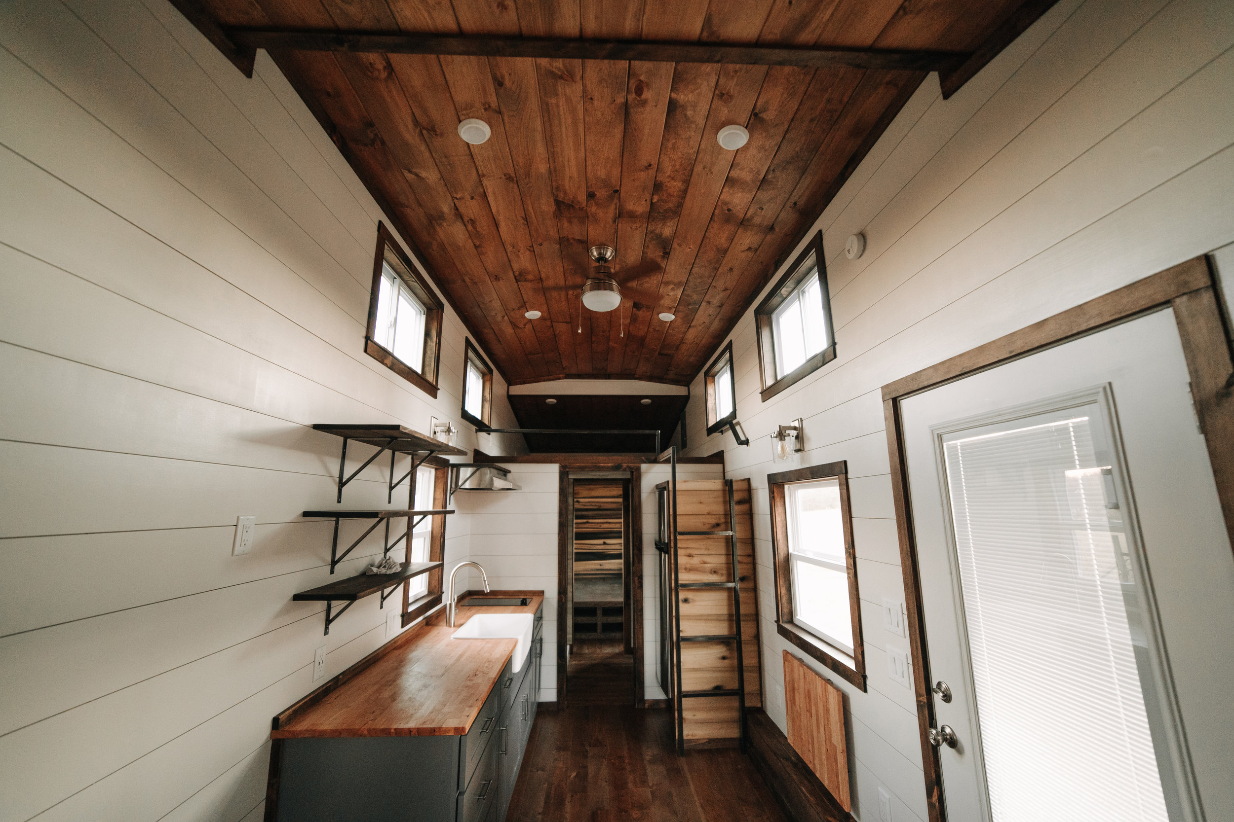 The Noah by Wind River Tiny Homes - birch hardwood flooring, ship lap, fold down table, custom welded steel ladder, gray shaker cabinets, butcher block counter, farmhouse sink