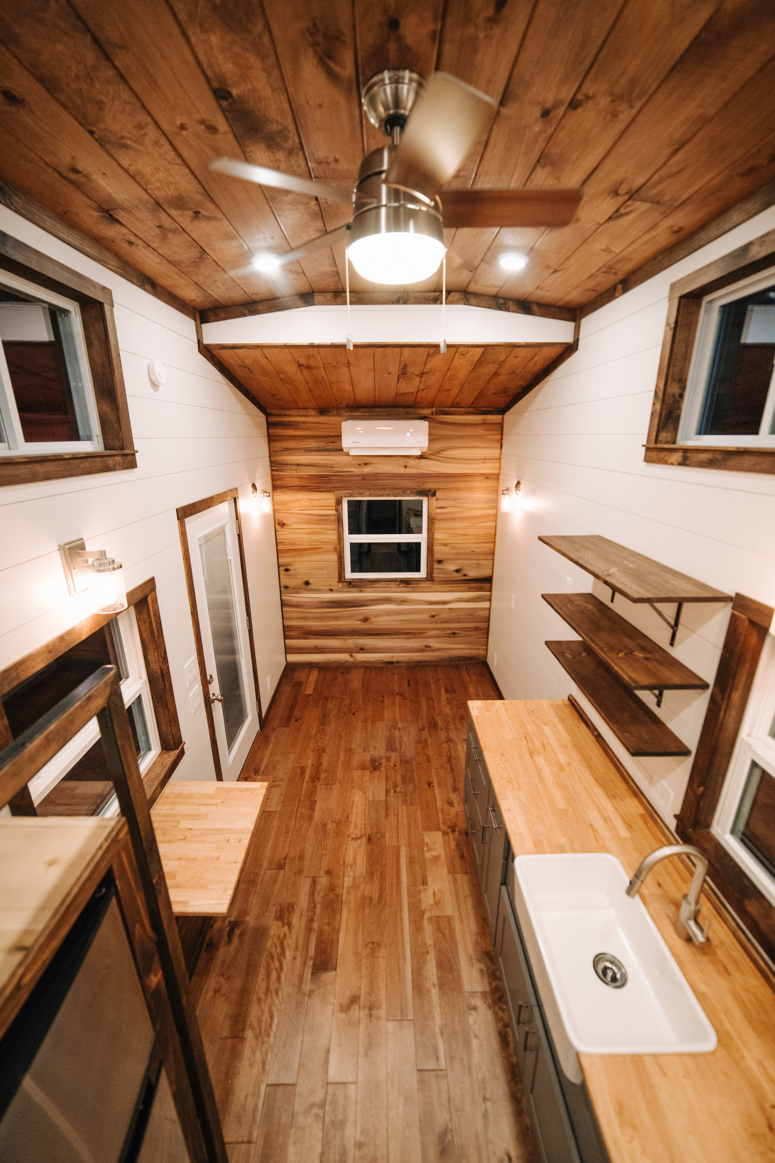 The Noah by Wind River Tiny Homes - farmhouse sink, butcher block counter, birch hardwood flooring, natural poplar accent wall, shiplap