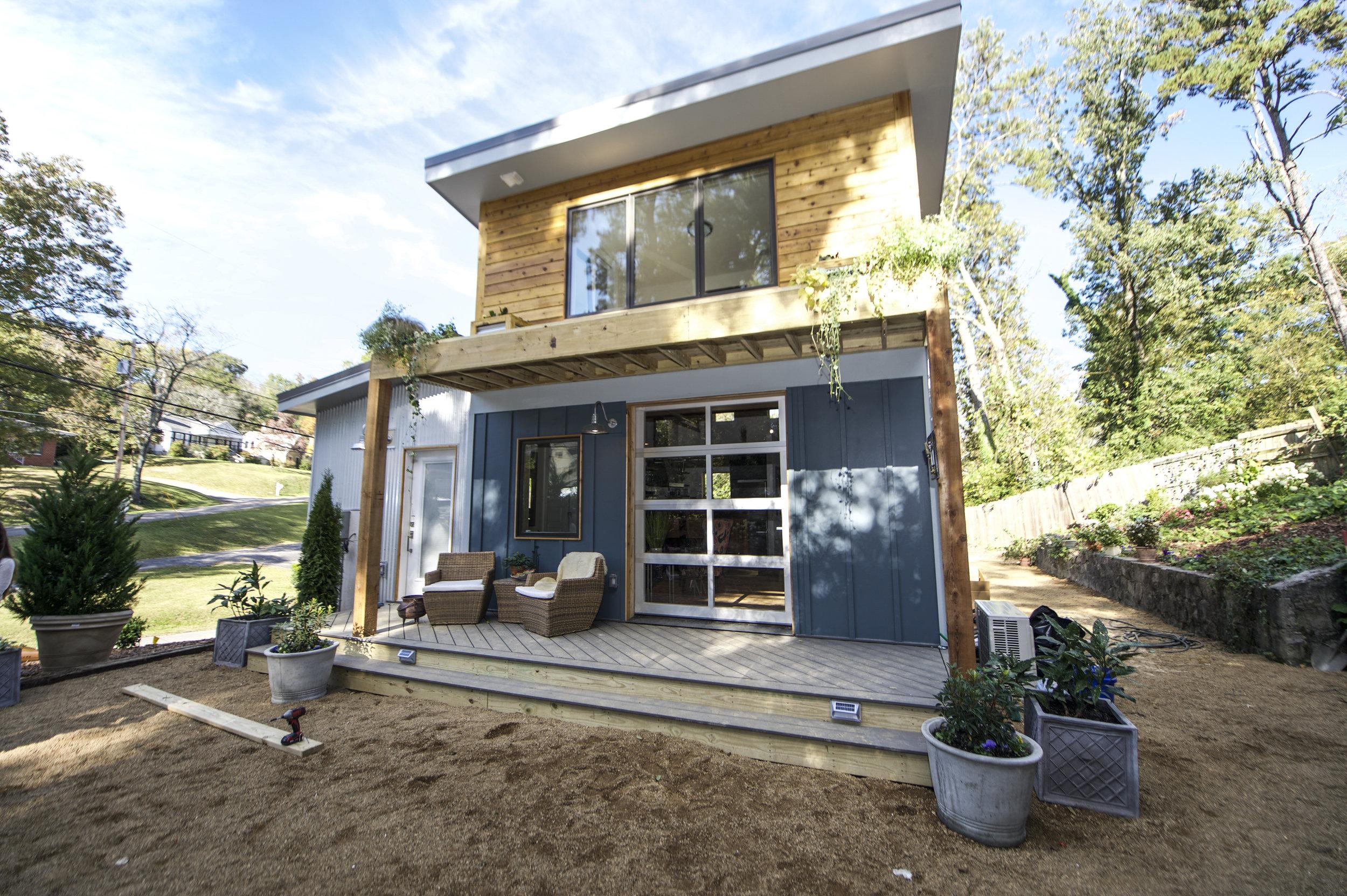 Casement windows in upstairs bedroom, solar powered lights on deck steps, aluminum clad glass pane garage door, cedar siding accents