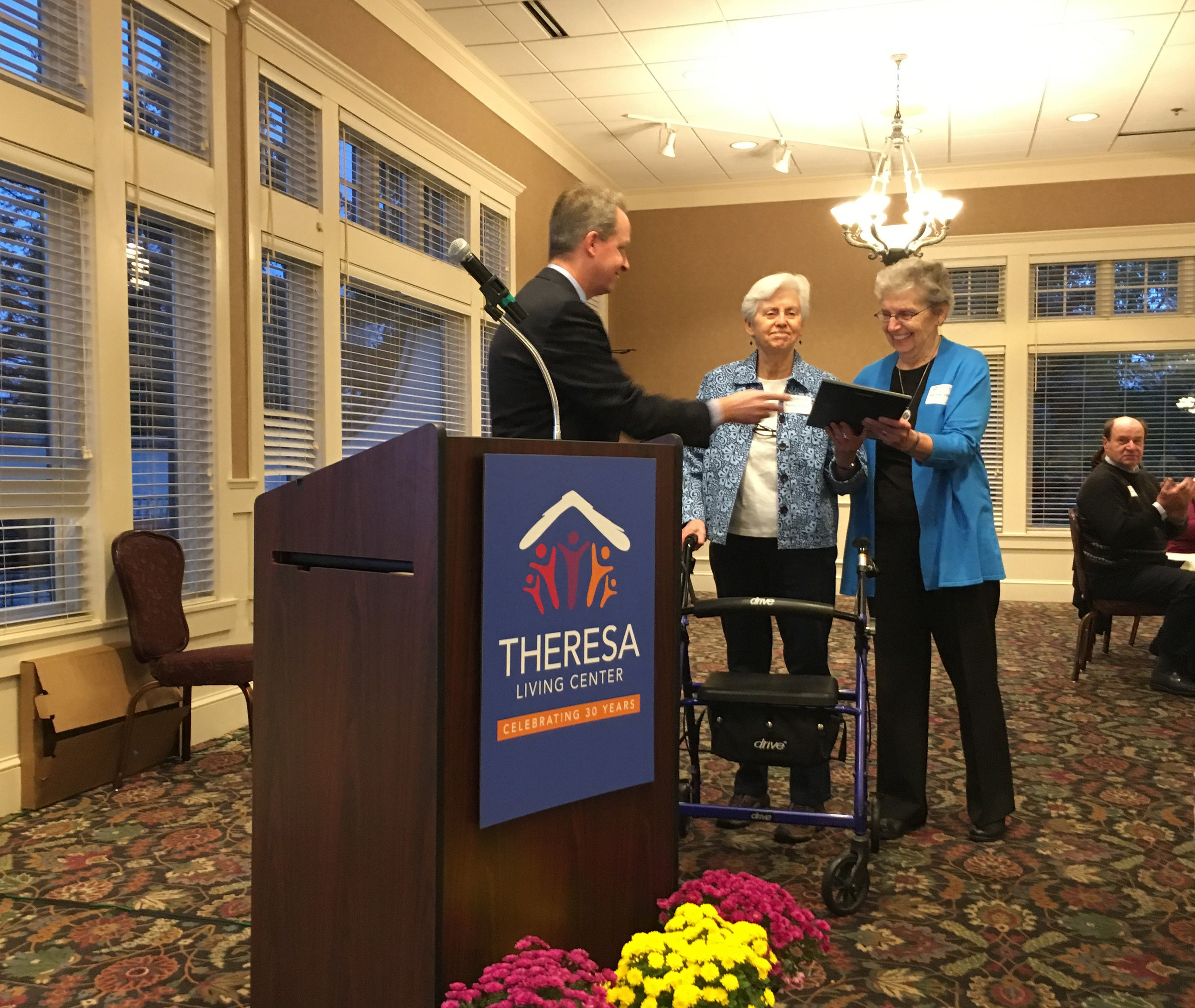 Board Chair Dennis WIlliams gives a plaque to Sisters Marilyn Orchard and Rita Jirik of the School Sisters of Notre Dame. Sisters Marilyn and Rita founded Theresa Living Center, which opened its doors to help homeless women and children in 1988 as a project to honor Mother Theresa Gerhardinger, an educator of girls and the foundress of their order.