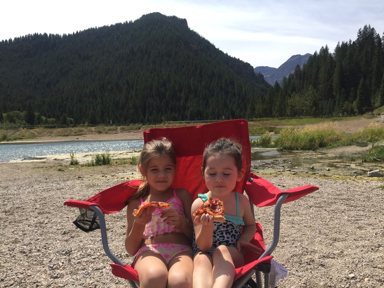 Lolah and Kaylie Palma taking a break from playing by eating pizza at Tibble Fork Lake Uinta National Forest.