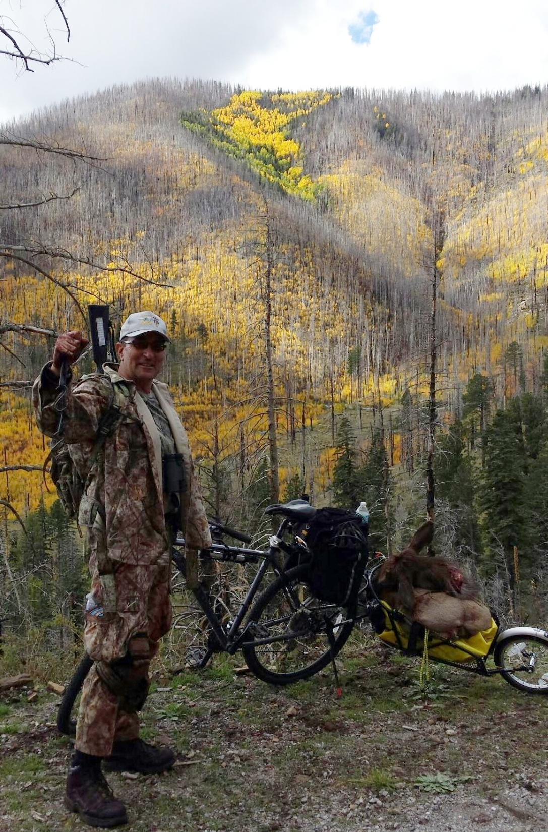 """""""I even combine my mountain biking and hunting, since most of the forest is closed to cars. It's great exercise."""" -- Martin Anaya  Photo, after the Schultz Fire Burn: Martin Anaya in 2016 taking the last load of successful elk harvest off the San Francisco Peaks on his mountain bike and trailer."""