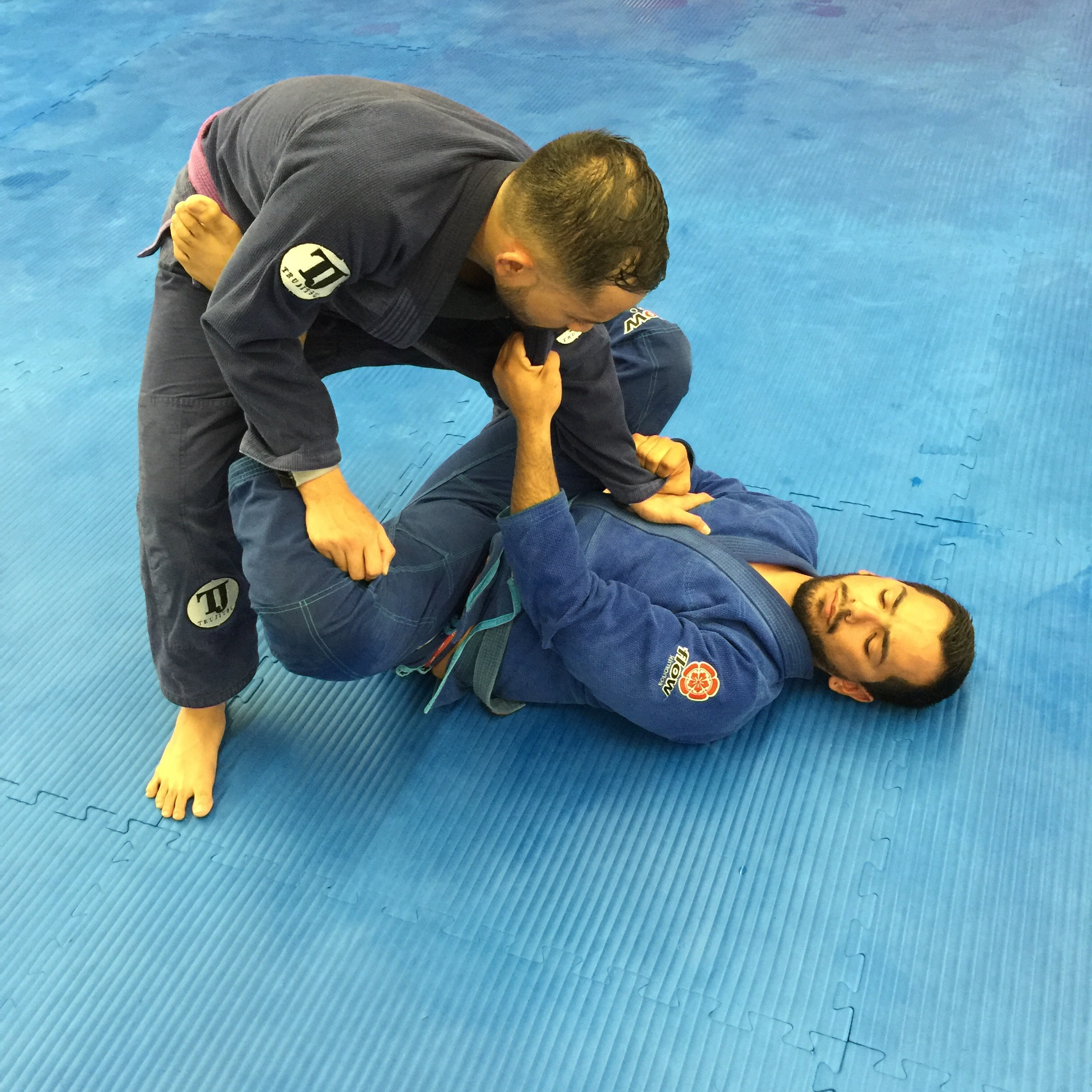 What not to do..  Leaning forward with your head causes you to reach with your arms. In addition to being In the range of your opponent's attacks, this also makes you top heavy where your opponent can play with your body weight and elevate you for a sweep.