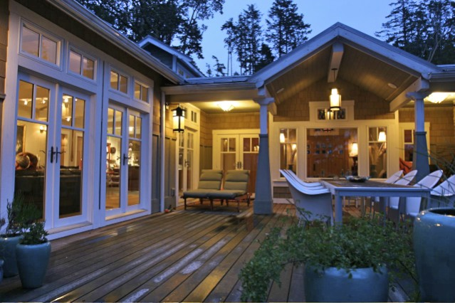 Back of house with covered back porch and rooms opening onto a huge entertaining deck.