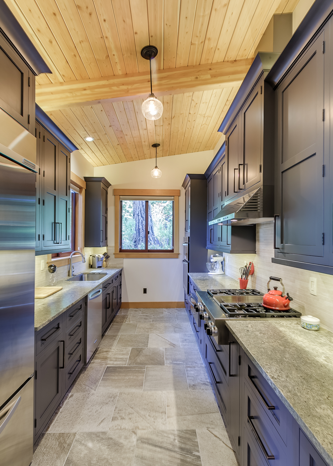 Narrow Kitchen works- the up lighting above the upper cabinets helps lift the lid of the ceiling to counter-act the dark cabinets.