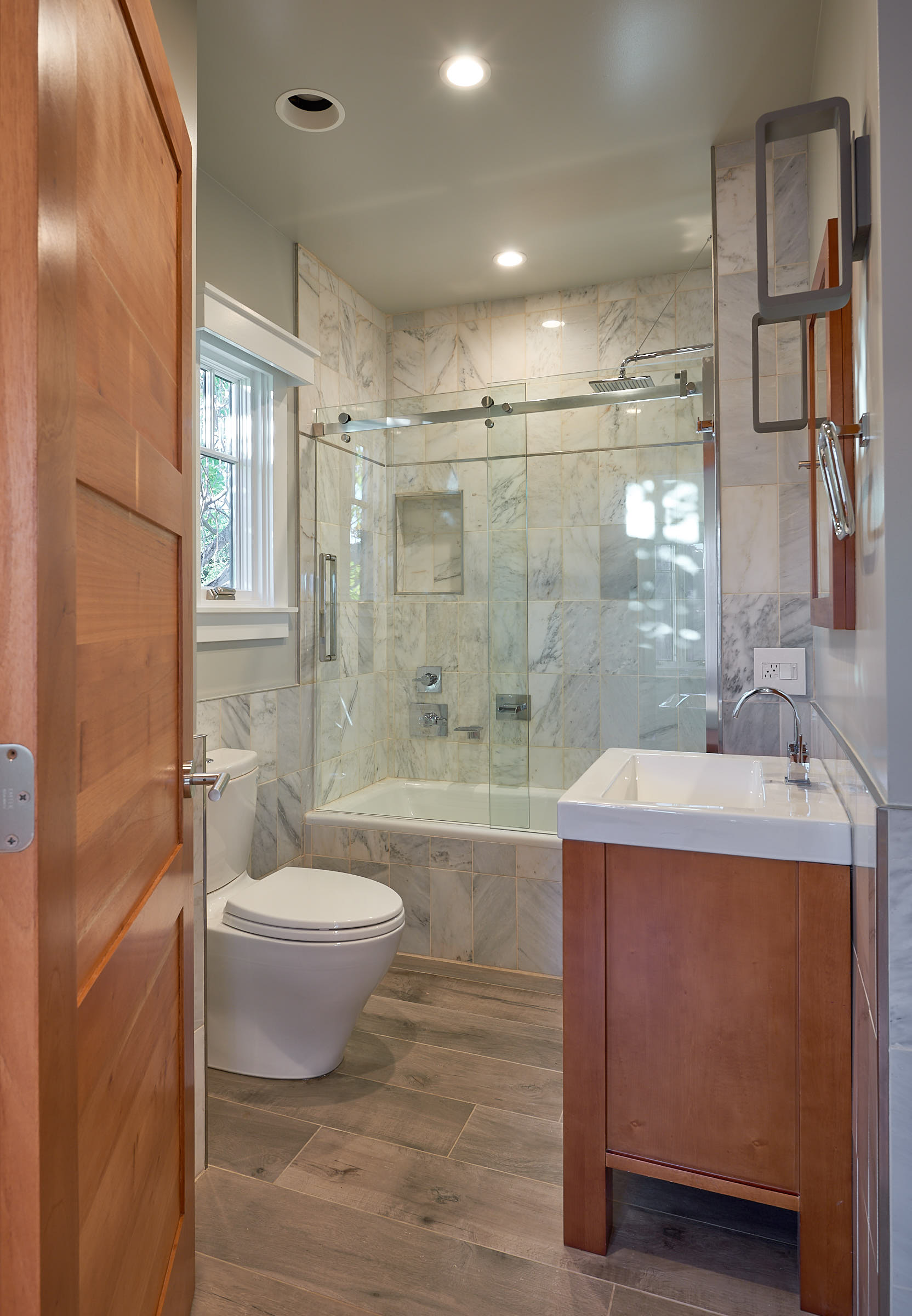 White Carrera Marble tile is a timeless material used in verticals, Porcelain tile floor looks like driftwood and contrasts nicely with the wood accents.