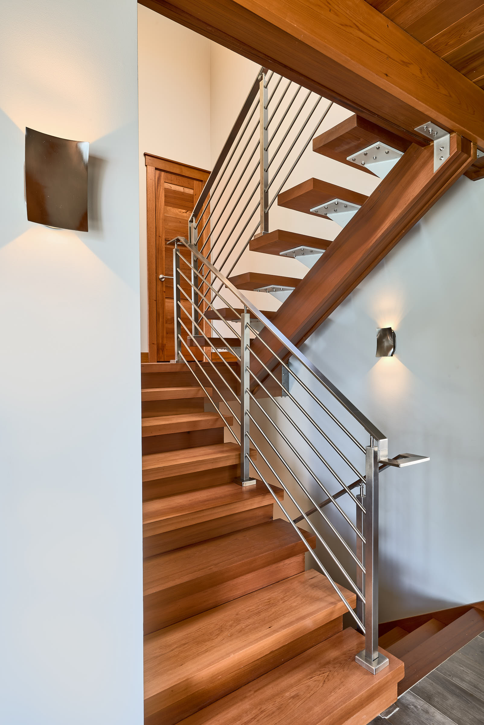 From the entry, the upper staircase treads float on a wood beam.
