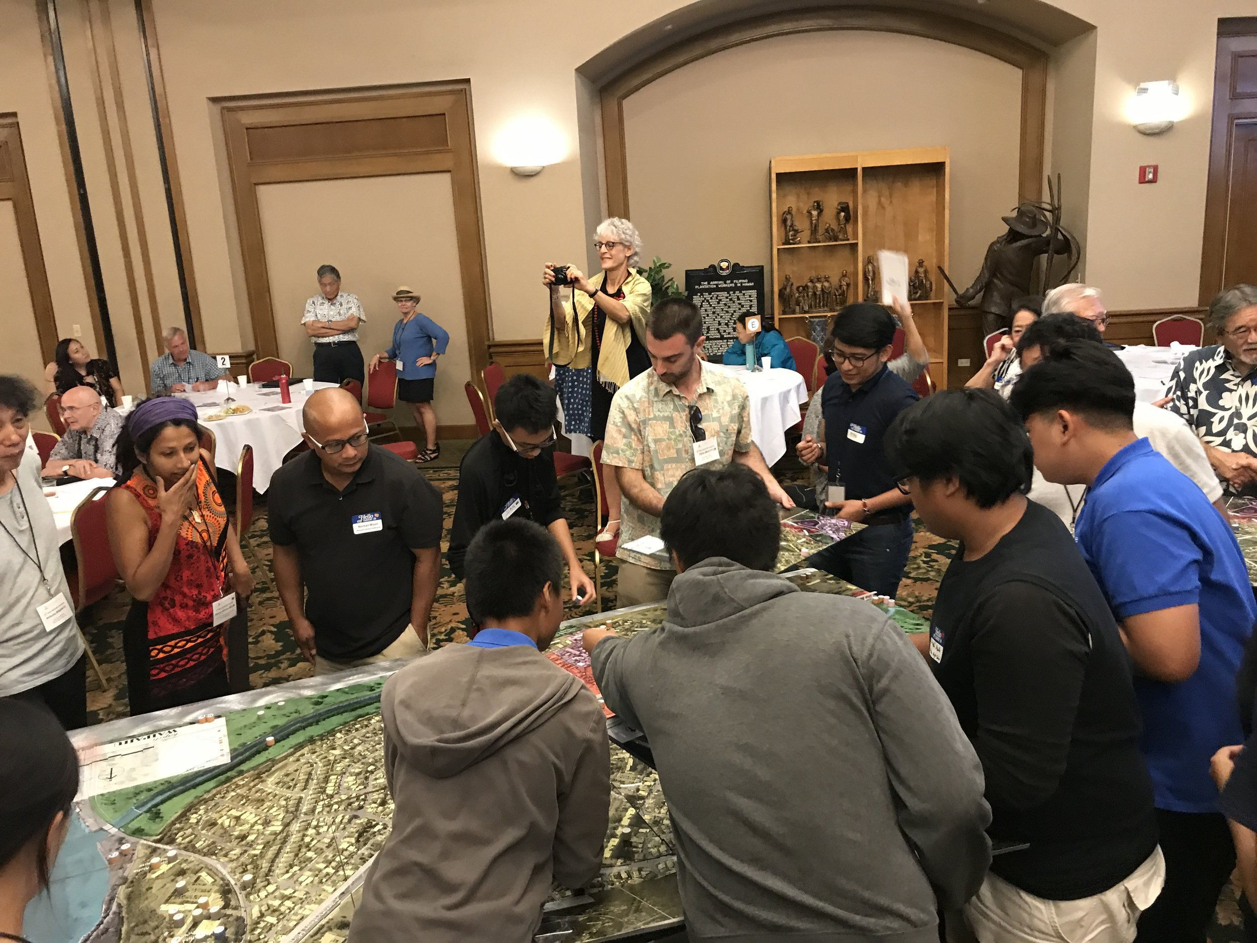 Workshop attendees gathering around Waipahu Town model