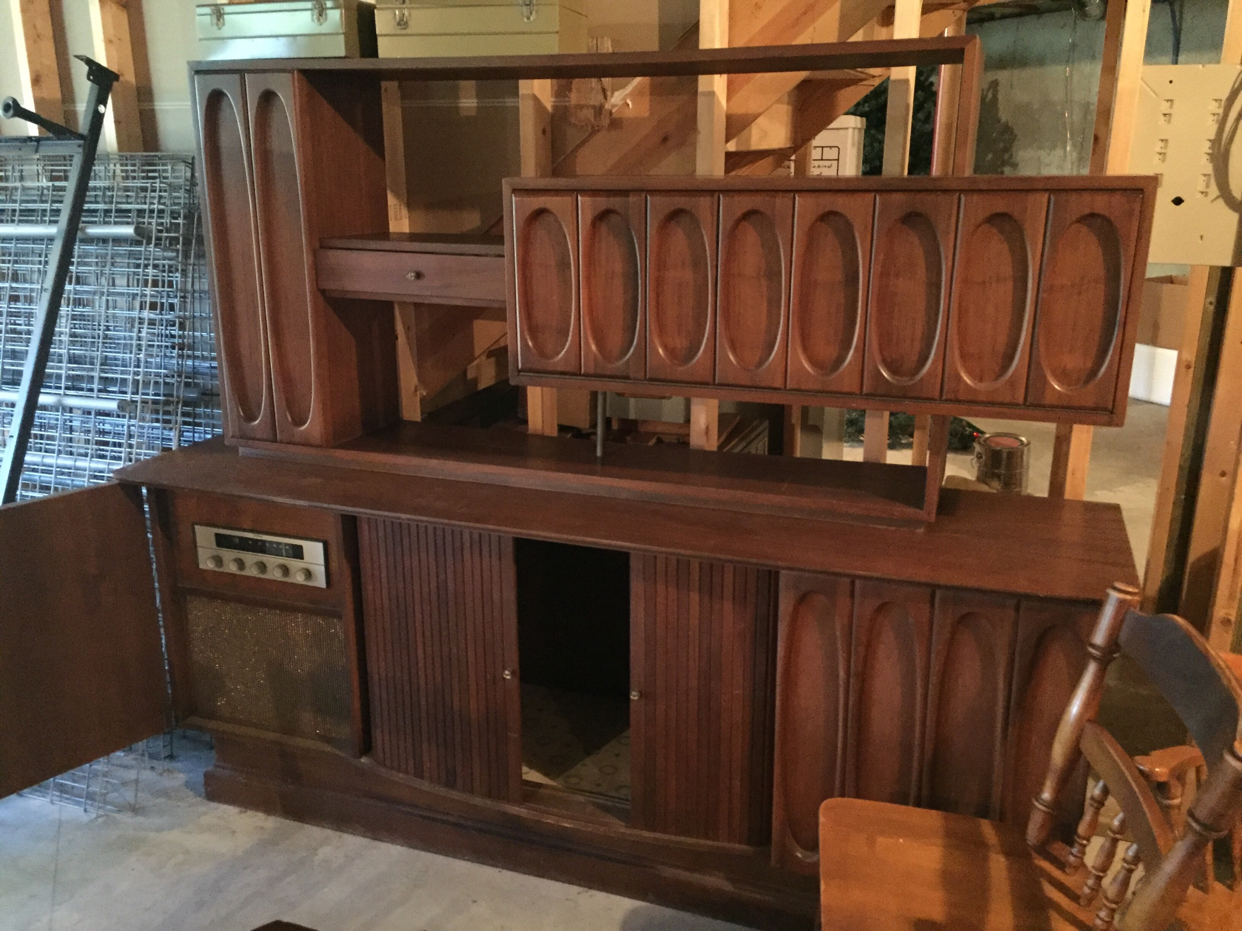 Amazing Walnut custom entertainment unit. This features built in speakers and receiver, pUll out for turntAble, tambour doors. The top cabinet has a bar area! I can't wait to get it home and cleaned up., test the audio equipmenT and report back. It is a 2 pc unit.
