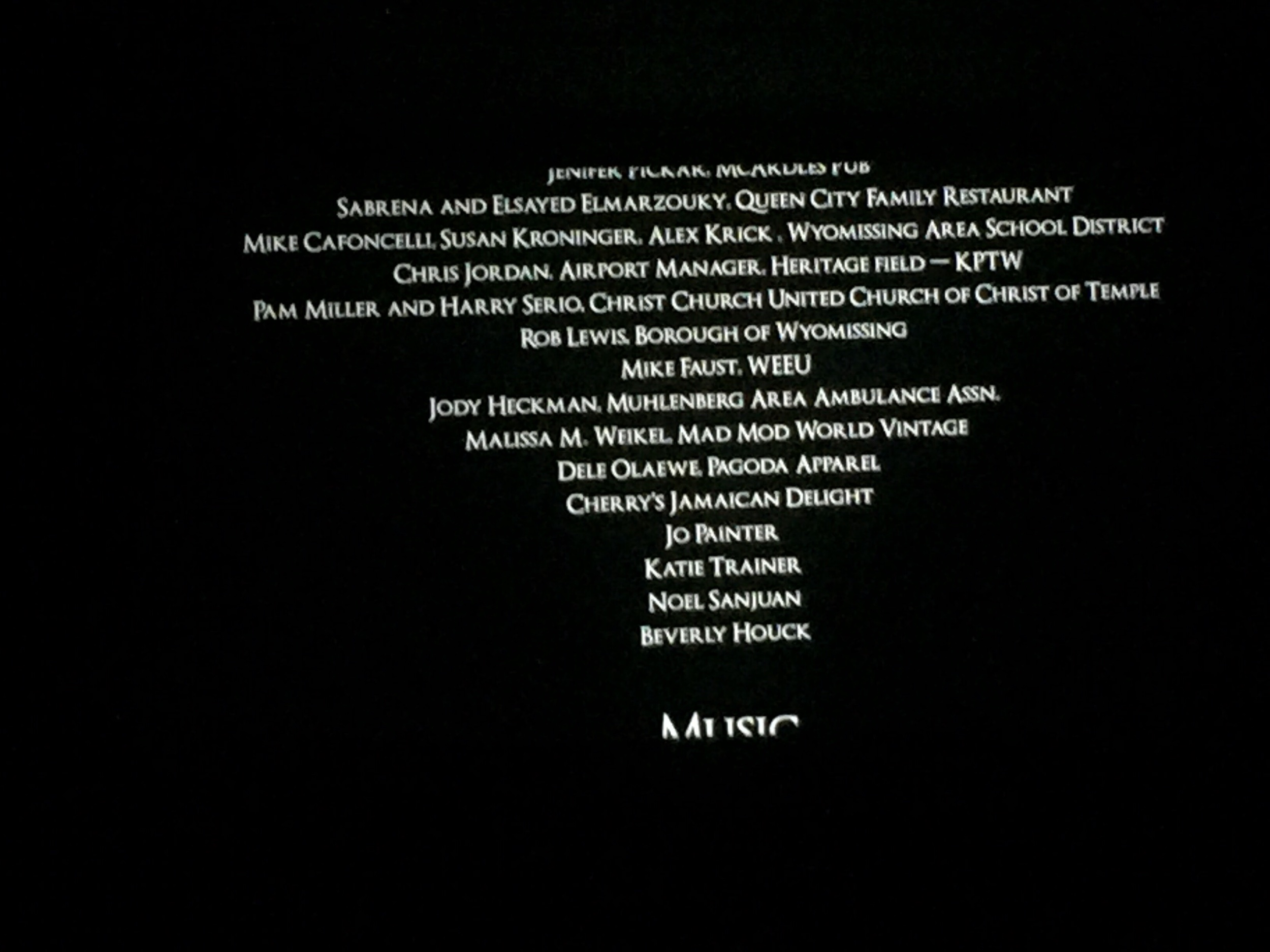 Credits from the film 'Dust Nuggets' scrolling on the big screen at the pre-screening with cast and crew.