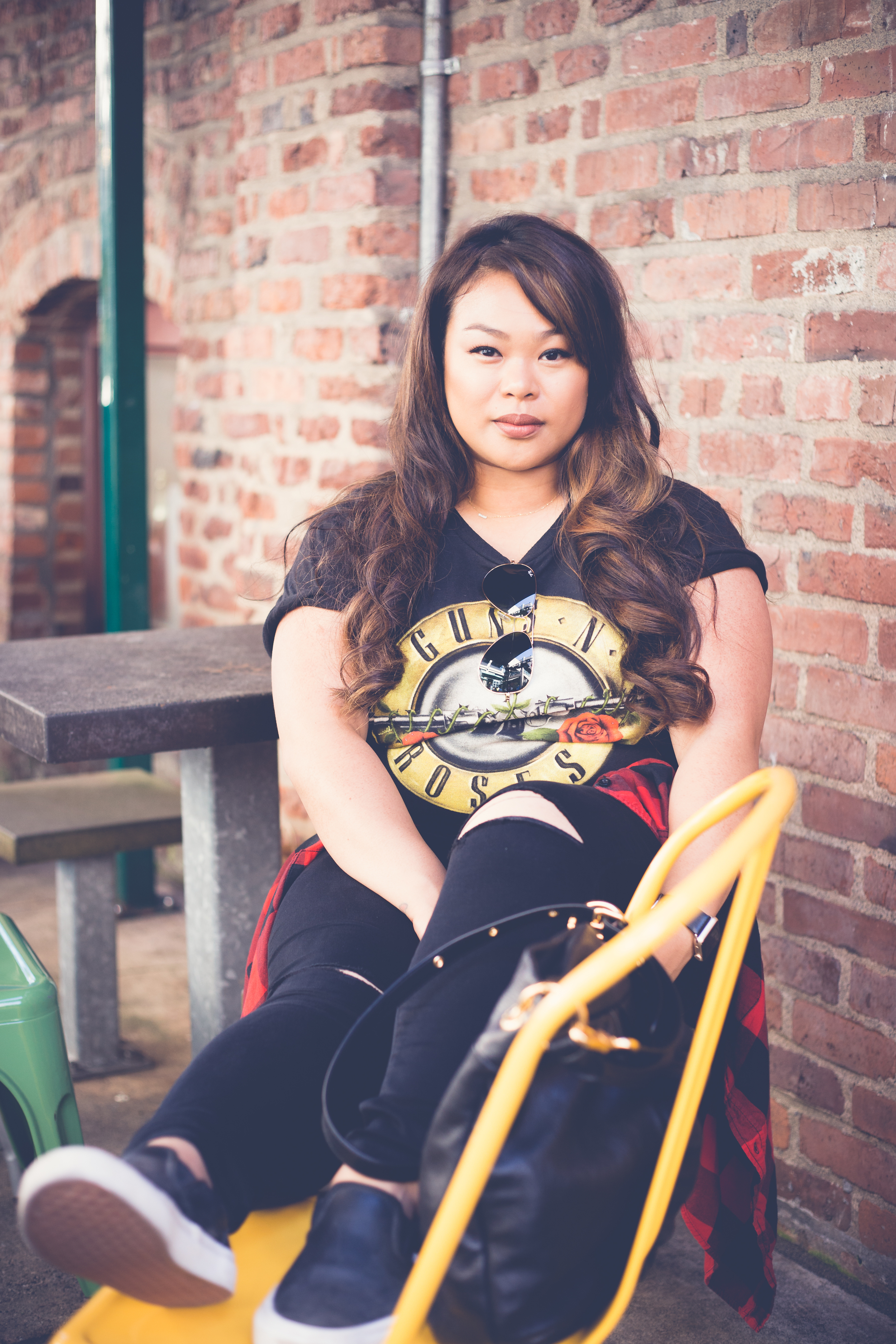 Street vibes against a cool brick wall. I love how the yellow chair compliments her t-shirt design.
