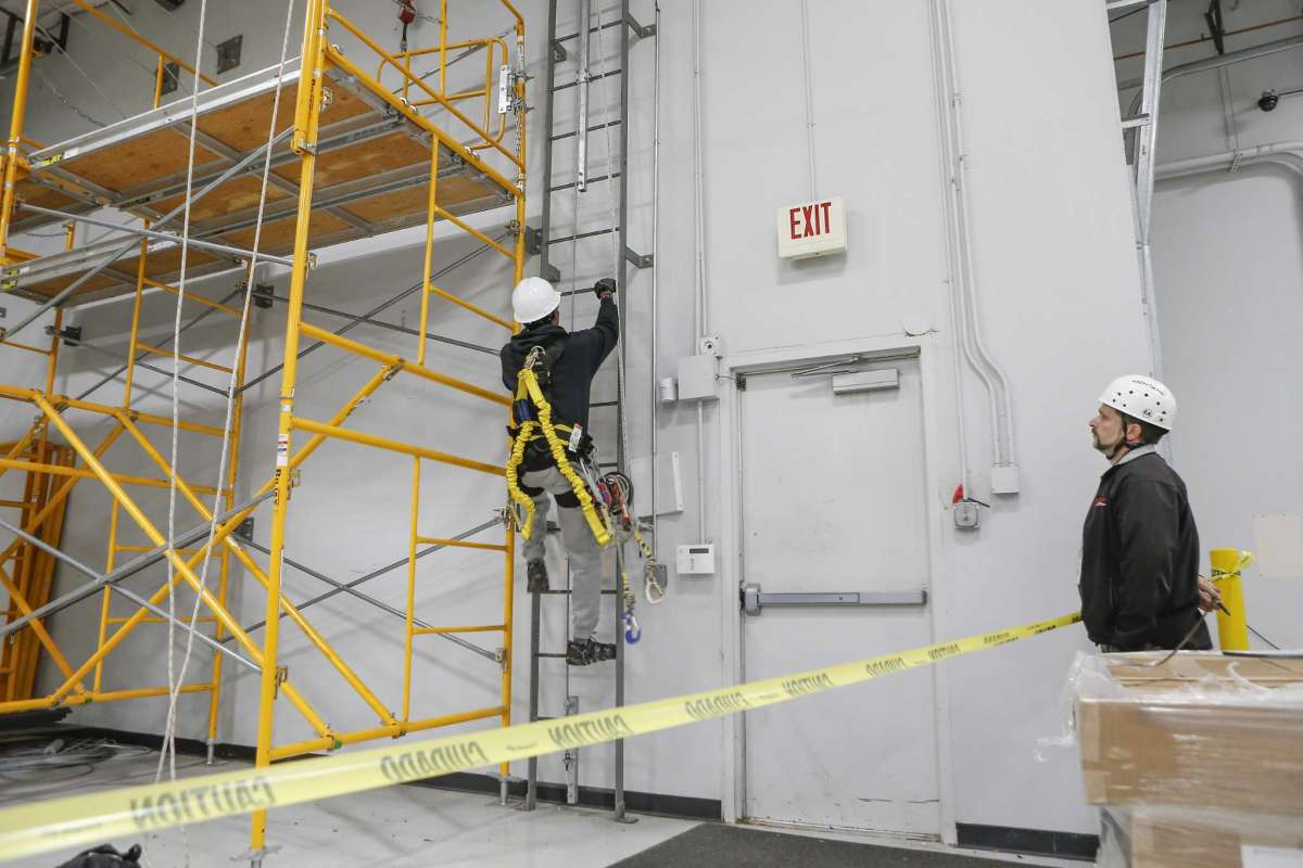 MIAT College of Technology Wind Turbine Instructor David Moriconi (right) watches a student performs a ladder exercise Wednesday, Oct. 24, 2018, in Houston. MIAT College of Technology has a seven-month wind power technician career training program.