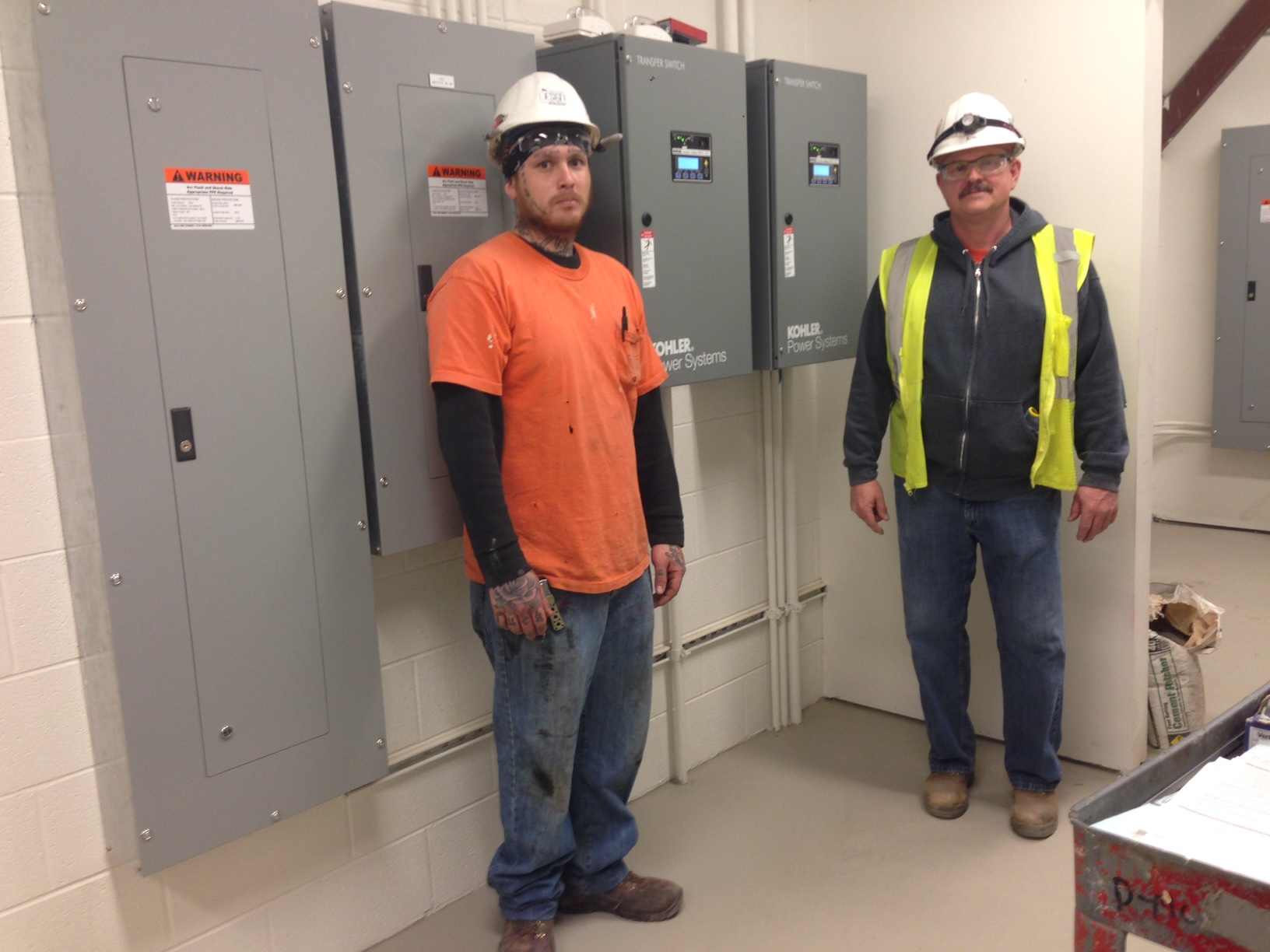 Aaron Coffey and Bill Stockdale standing in front of the panel boxes they worked on.