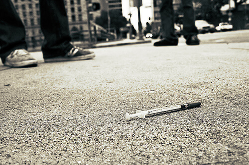 A used syringe that was possibly filled with illegal drugs laying on the street near some people.
