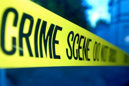 """Yellow crime scene tape that says """"Crime scene do not cross""""."""