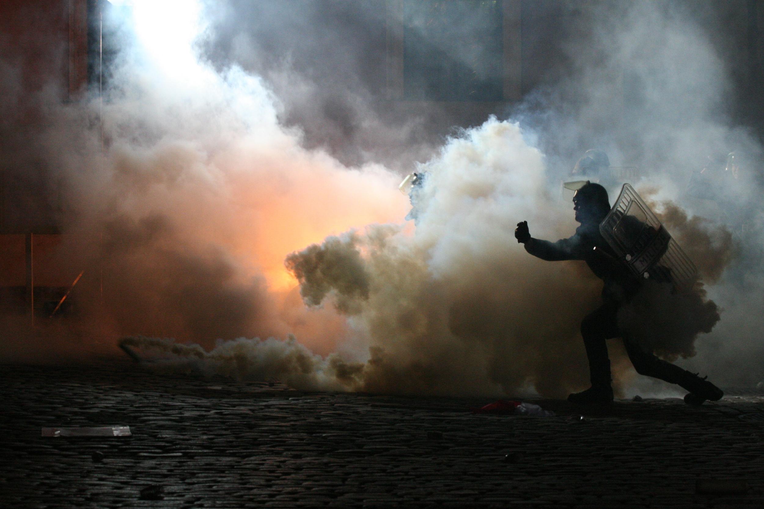 Swat team police running around in clouds of tear gas.